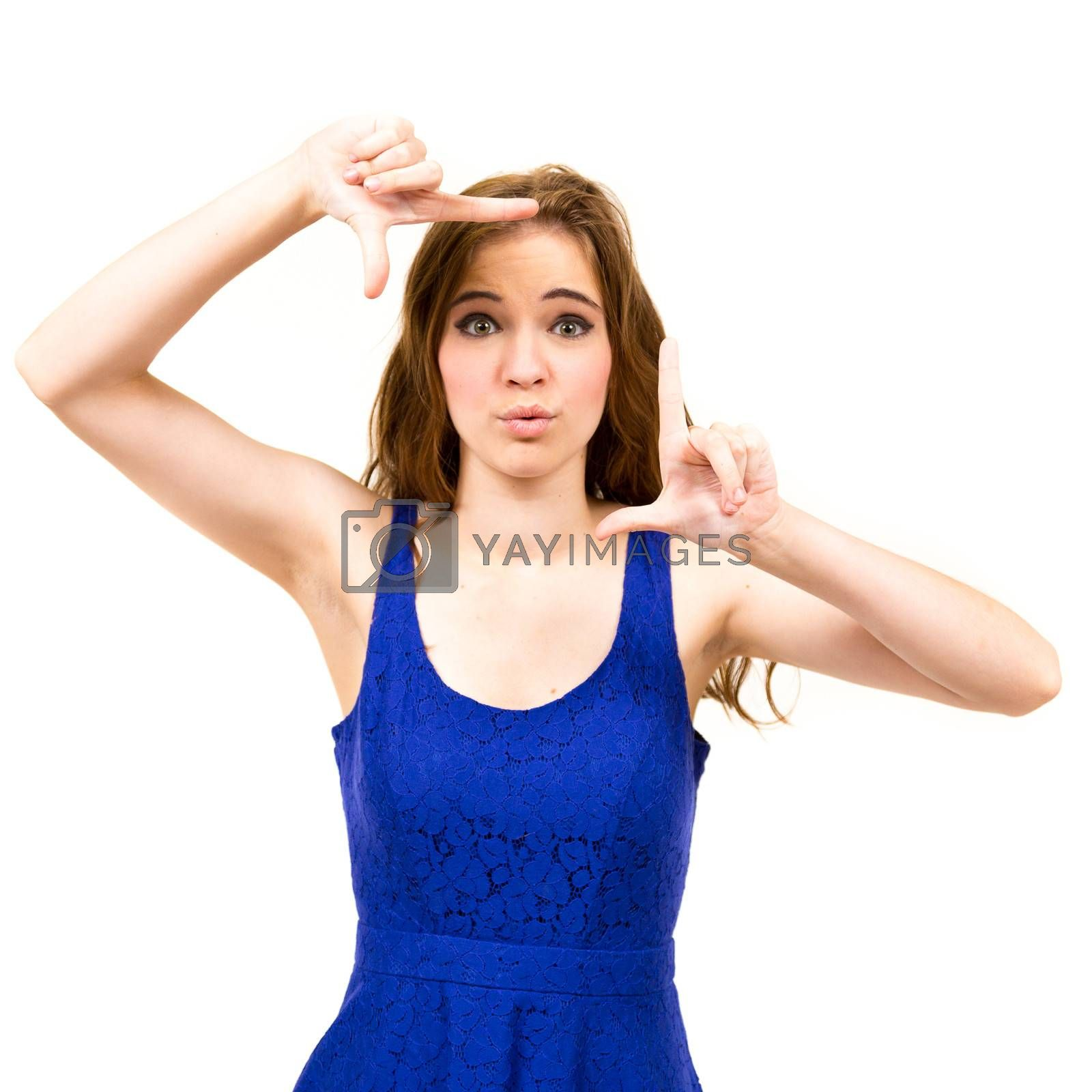 An attractive teen poses for a photo indoors in a lighting studio against a white background with a fashion style feel to the image.