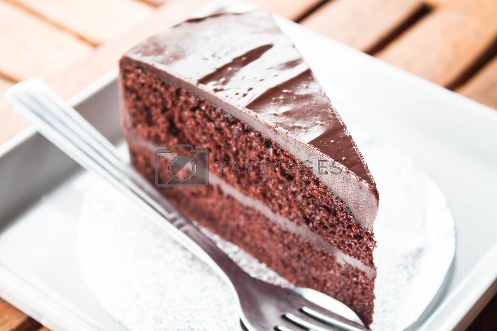 Chocolate cake serving on white plate with spoon and fork