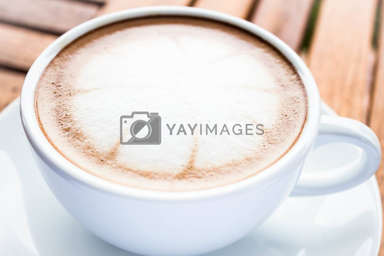 Serving cup of hot cafe mocha on wooden table