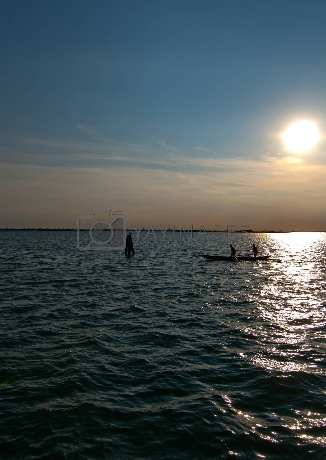 Italy Venice lagune view from  Burano island at sunset with boat silouette