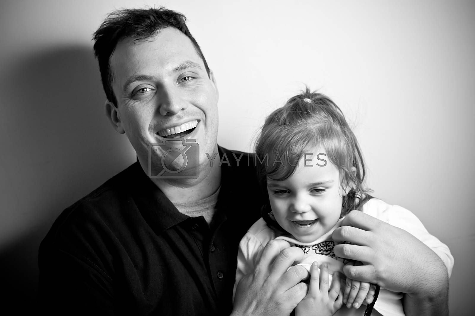 A young happy toddler aged little girl posing with her daddy. Black and white.