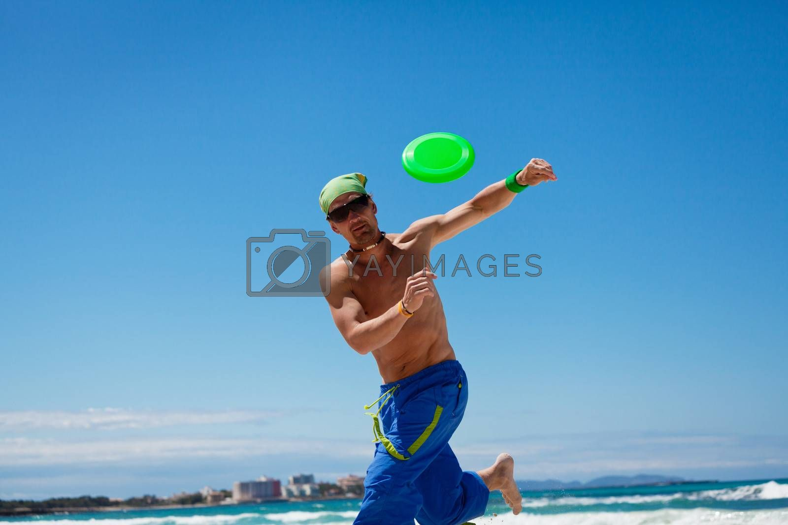 attractive man playing frisby on beach in summer sport fitness jump