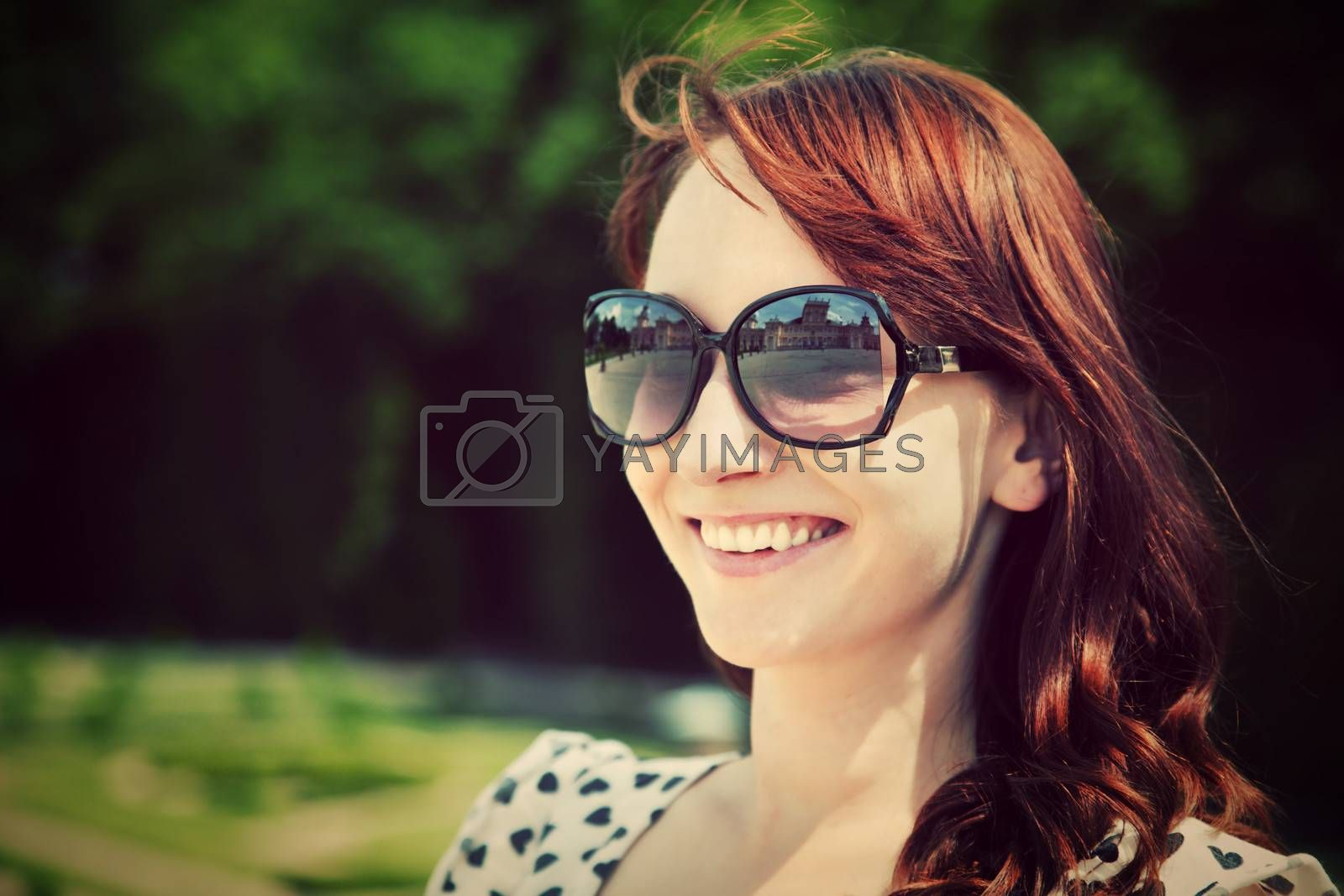 Young beautiful woman in sunglasses smiling in a summer park. Portrait