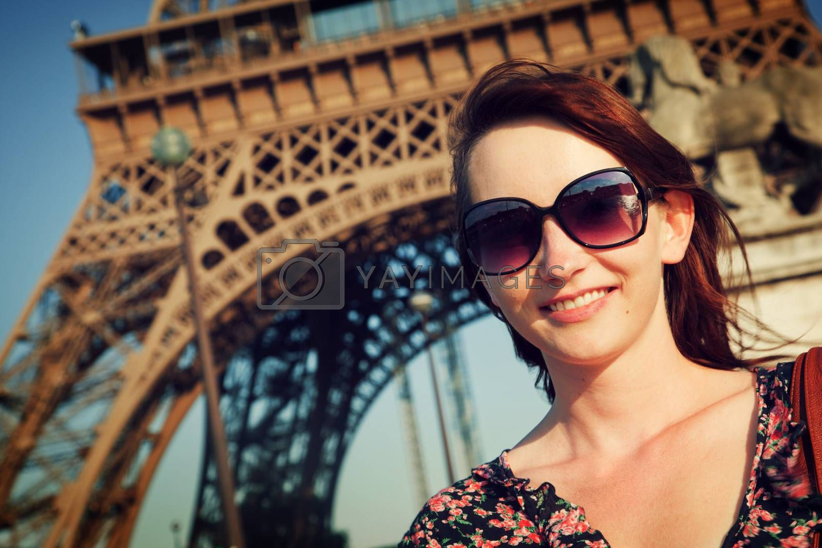 Young attractive happy woman smiling and looking at the camera against Eiffel Tower in Paris, France