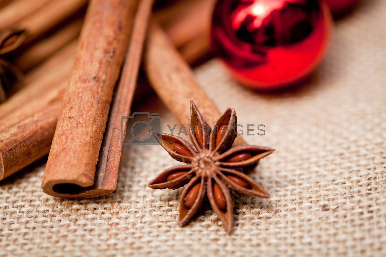 christmas decoration cinnamon anise baubles in red macro closeup