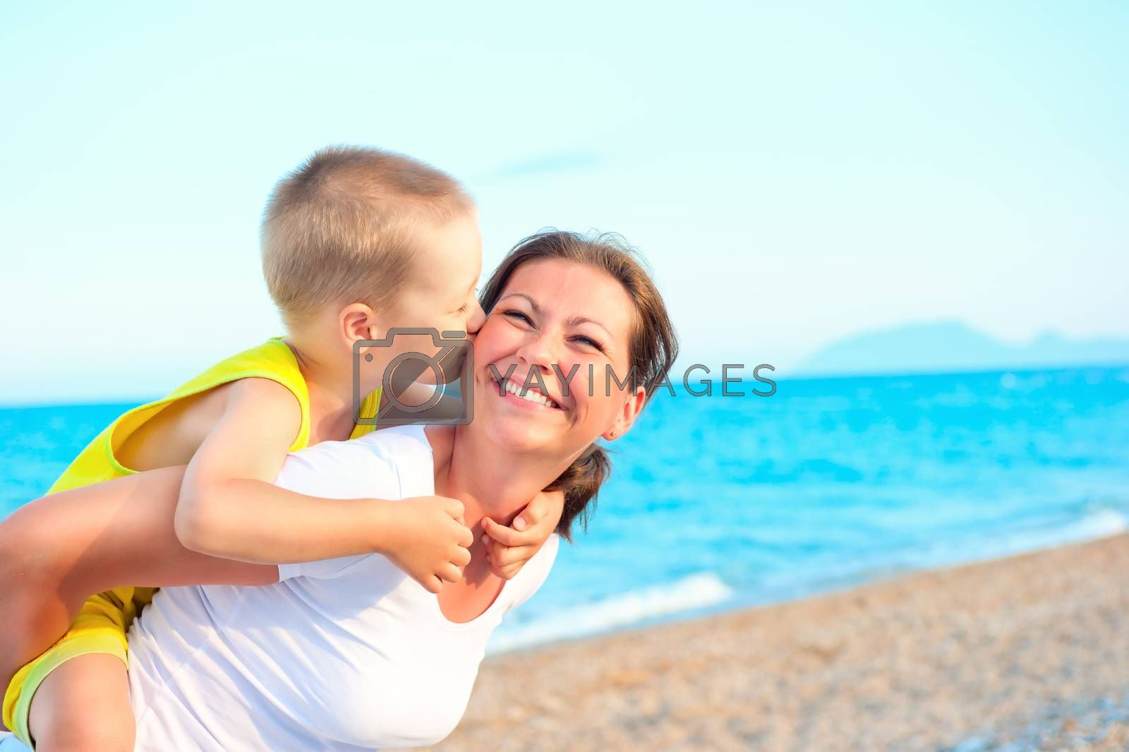 son kissing and hugging her mother on the background of the sea