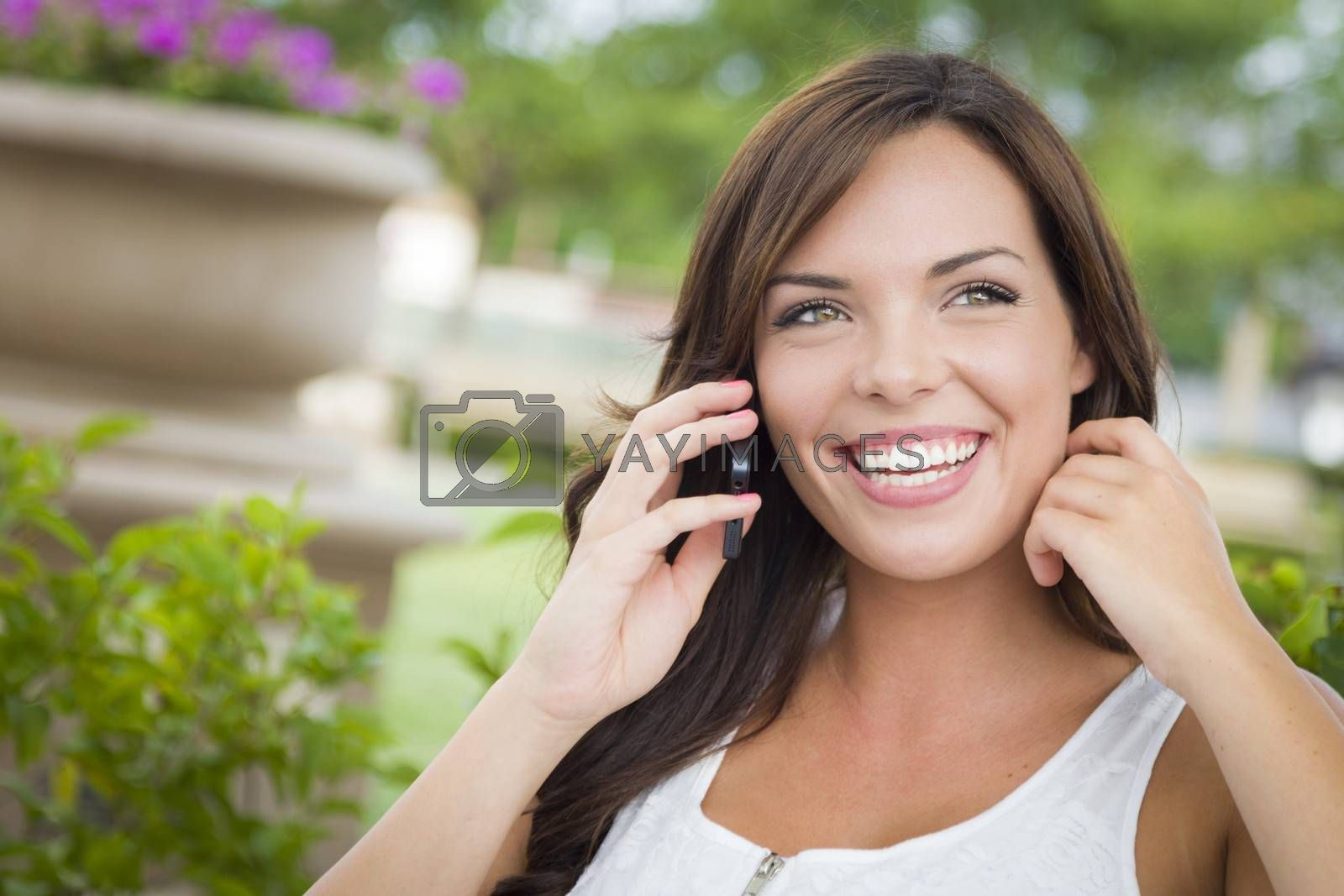 Attractive Young Adult Female Talking on Cell Phone Outdoors on Bench.
