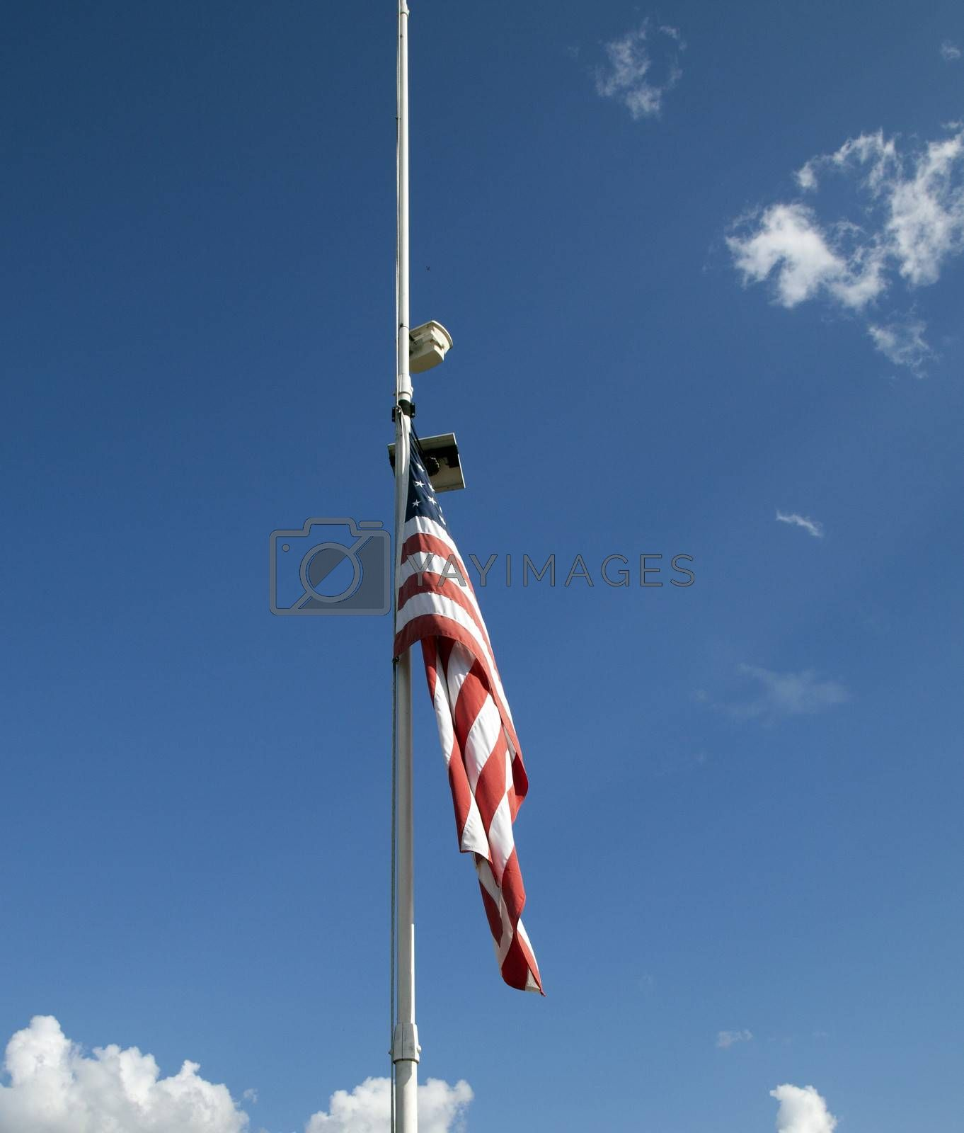 American flag at half mast with in the sky background