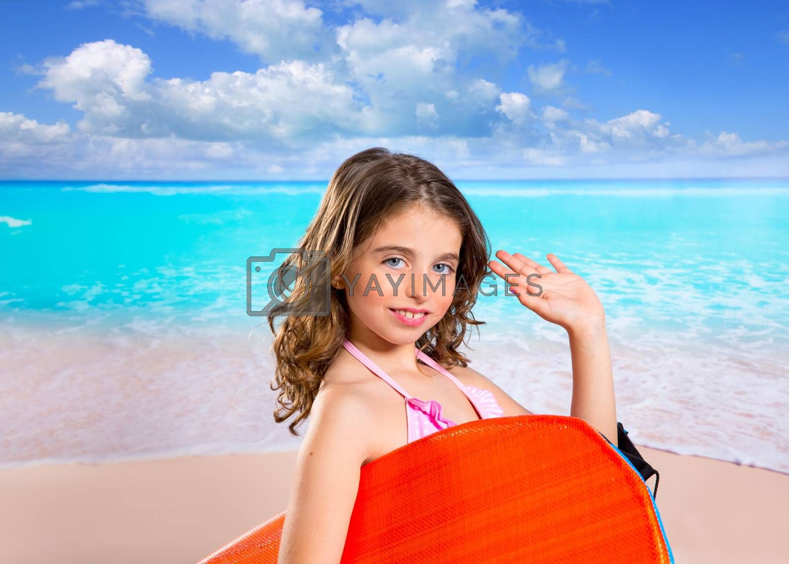 Children fashion surfer girl in tropical turquoise beach vacation with greeting hand