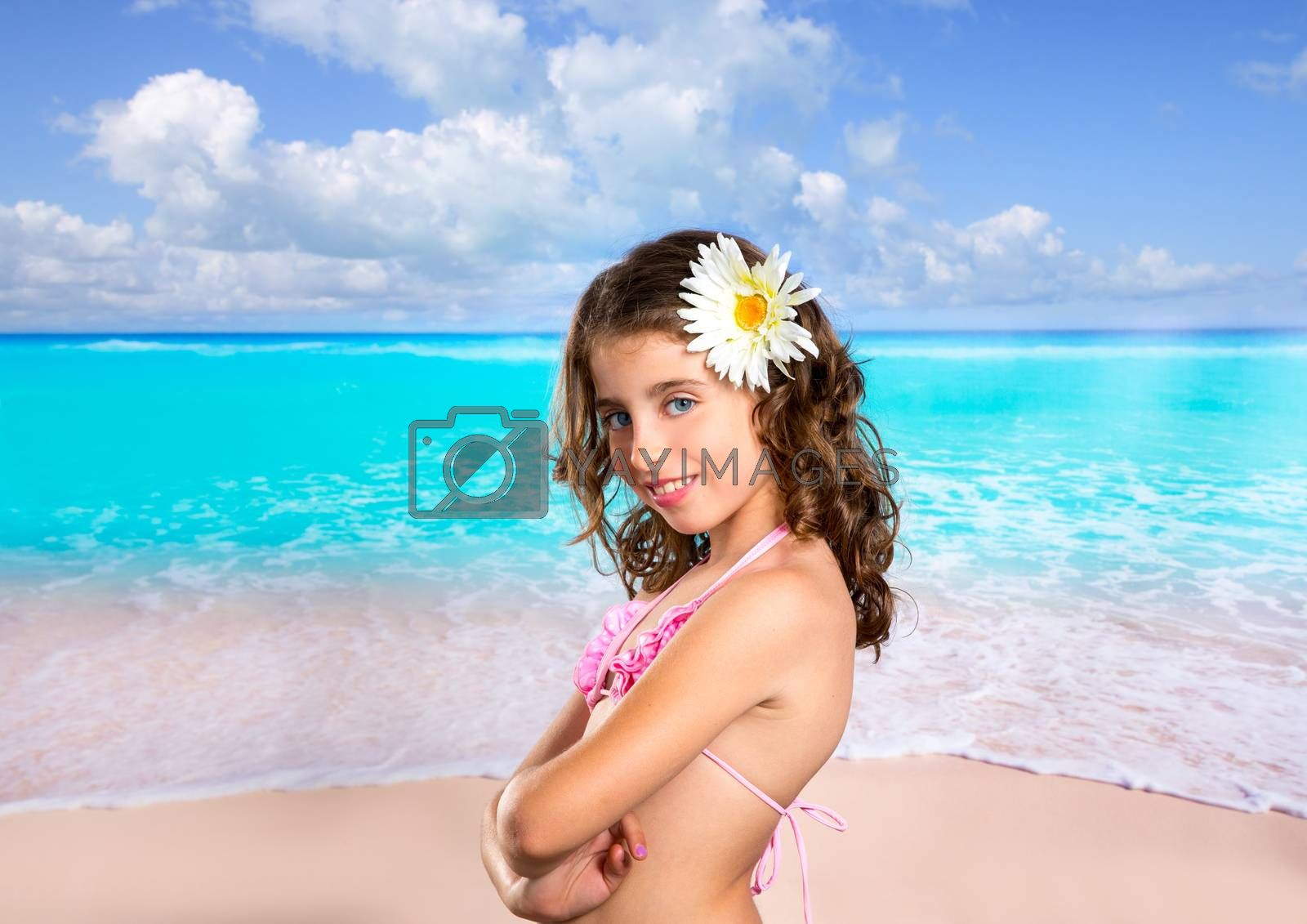 Brunette girl in tropical beach with daisy flower happy for vacation