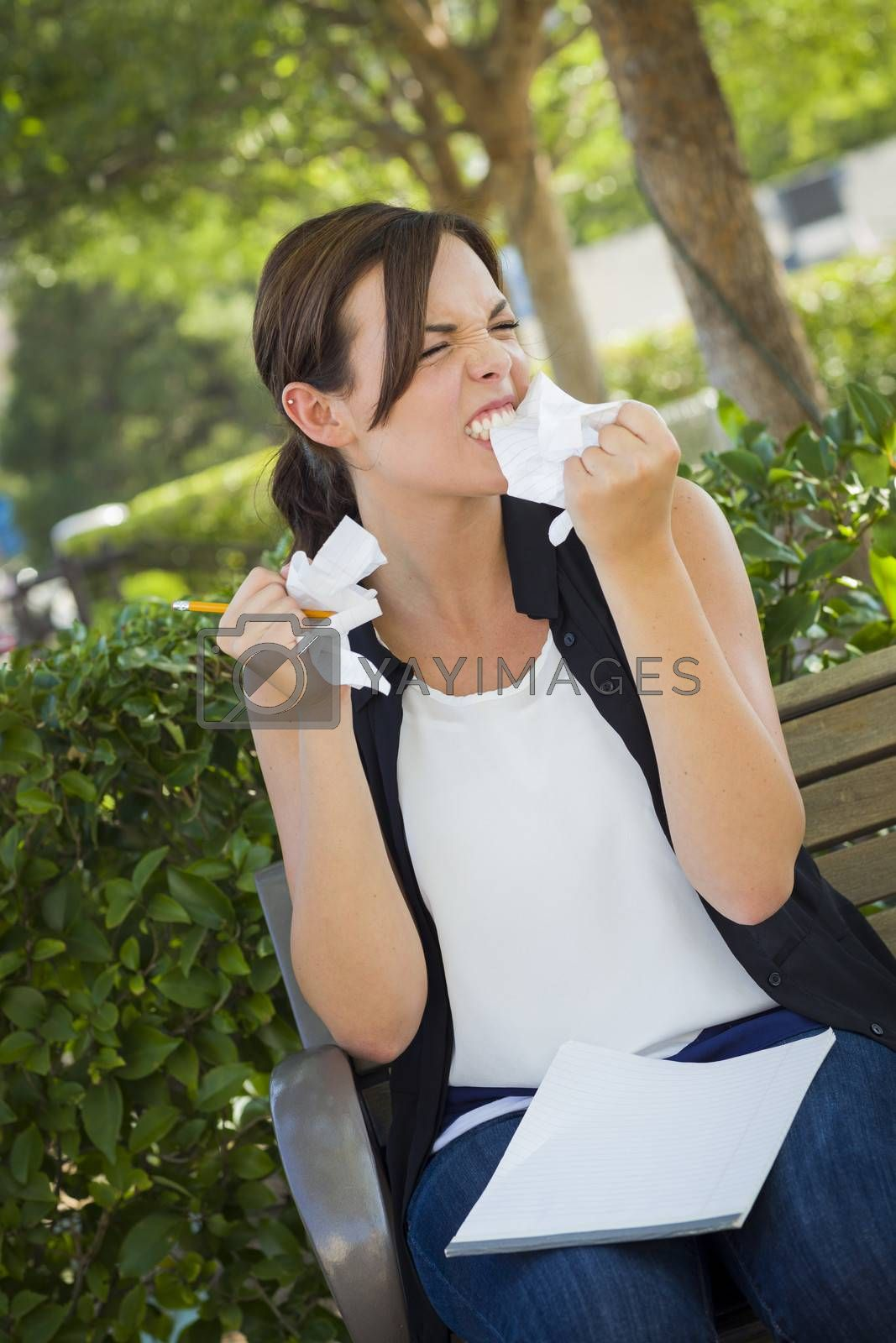 Frustrated and Upset Young Woman with Pencil and Crumpled Paper in Her Hand Sitting on Bench Outside.