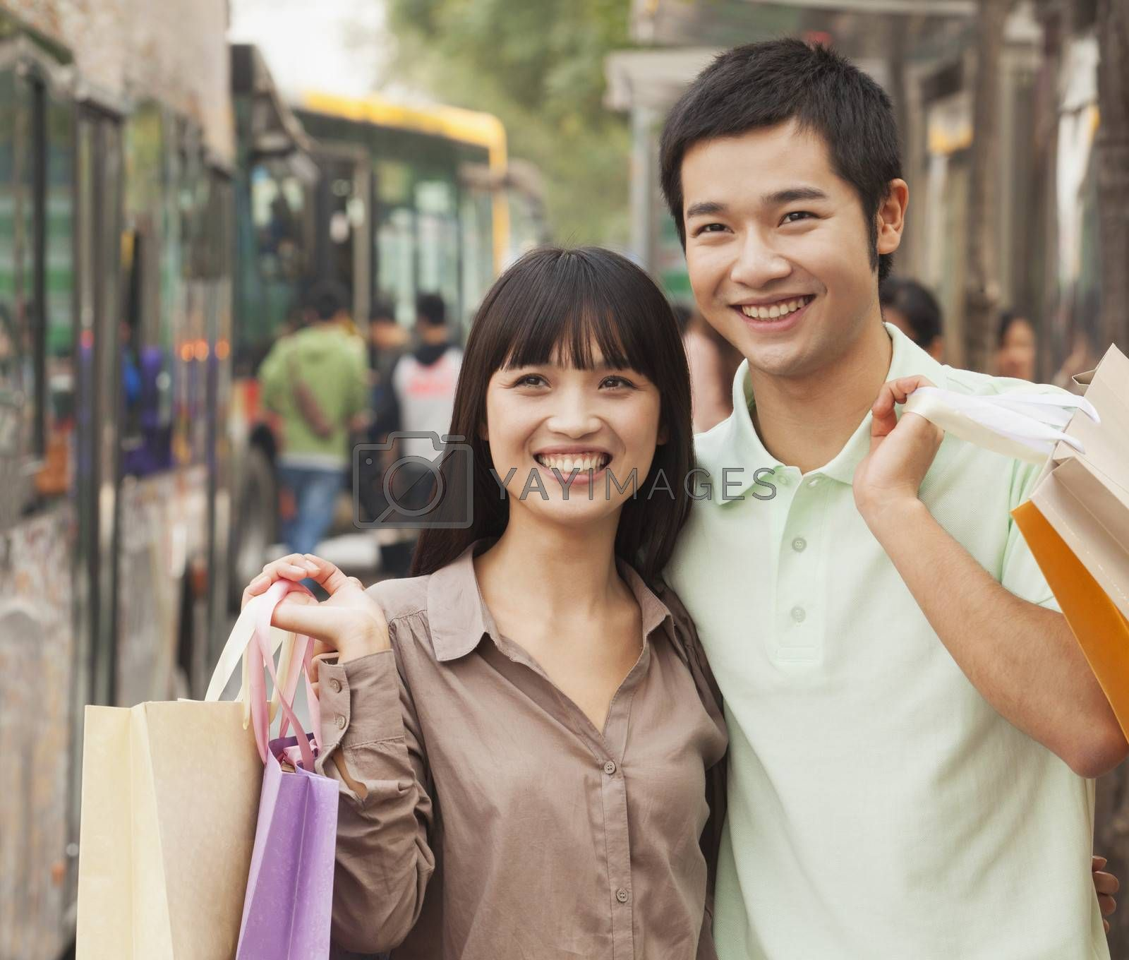 Portrait of smiling young couple at the bus stop, Beijing, China