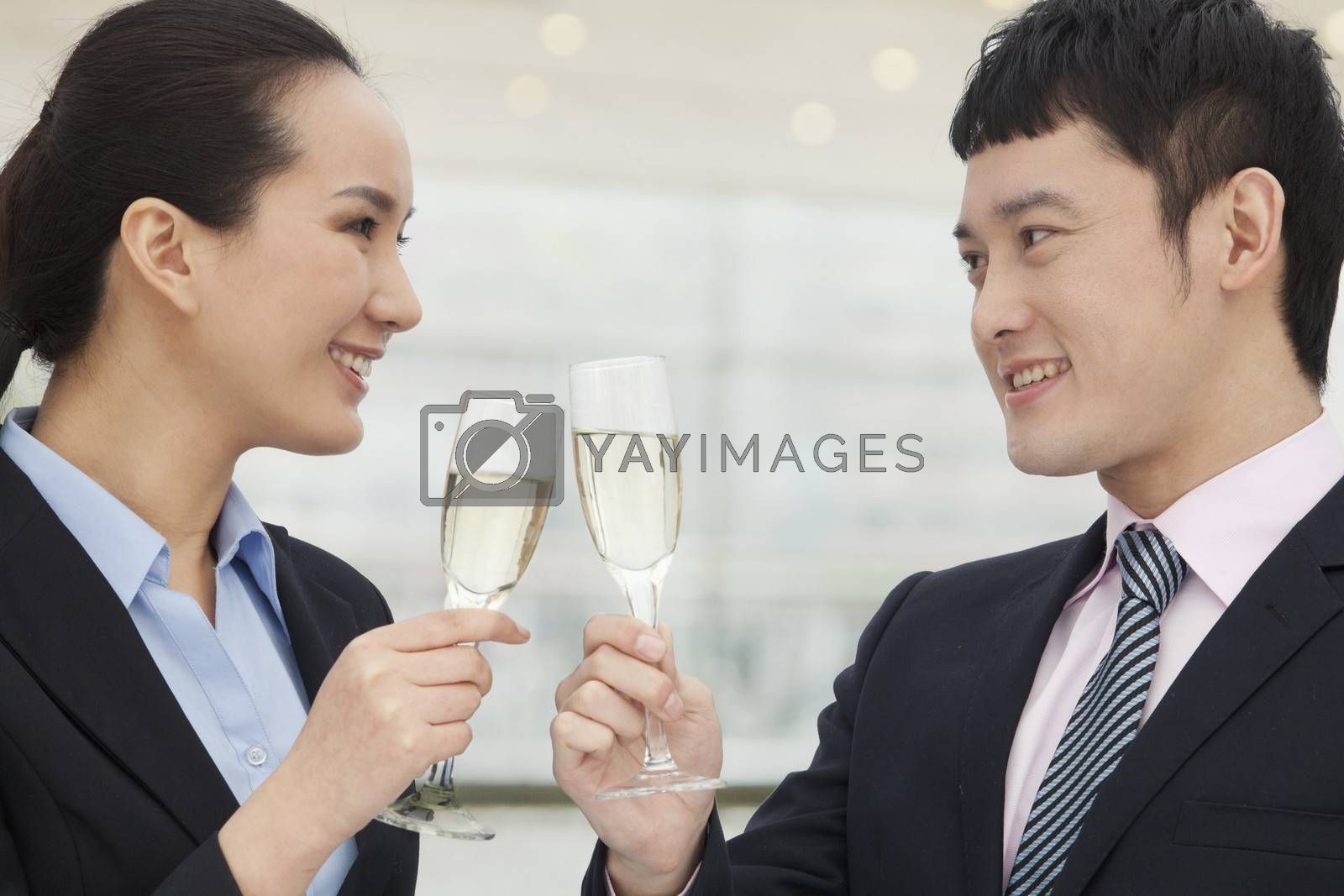 Young business man and woman toasting with champagne flutes