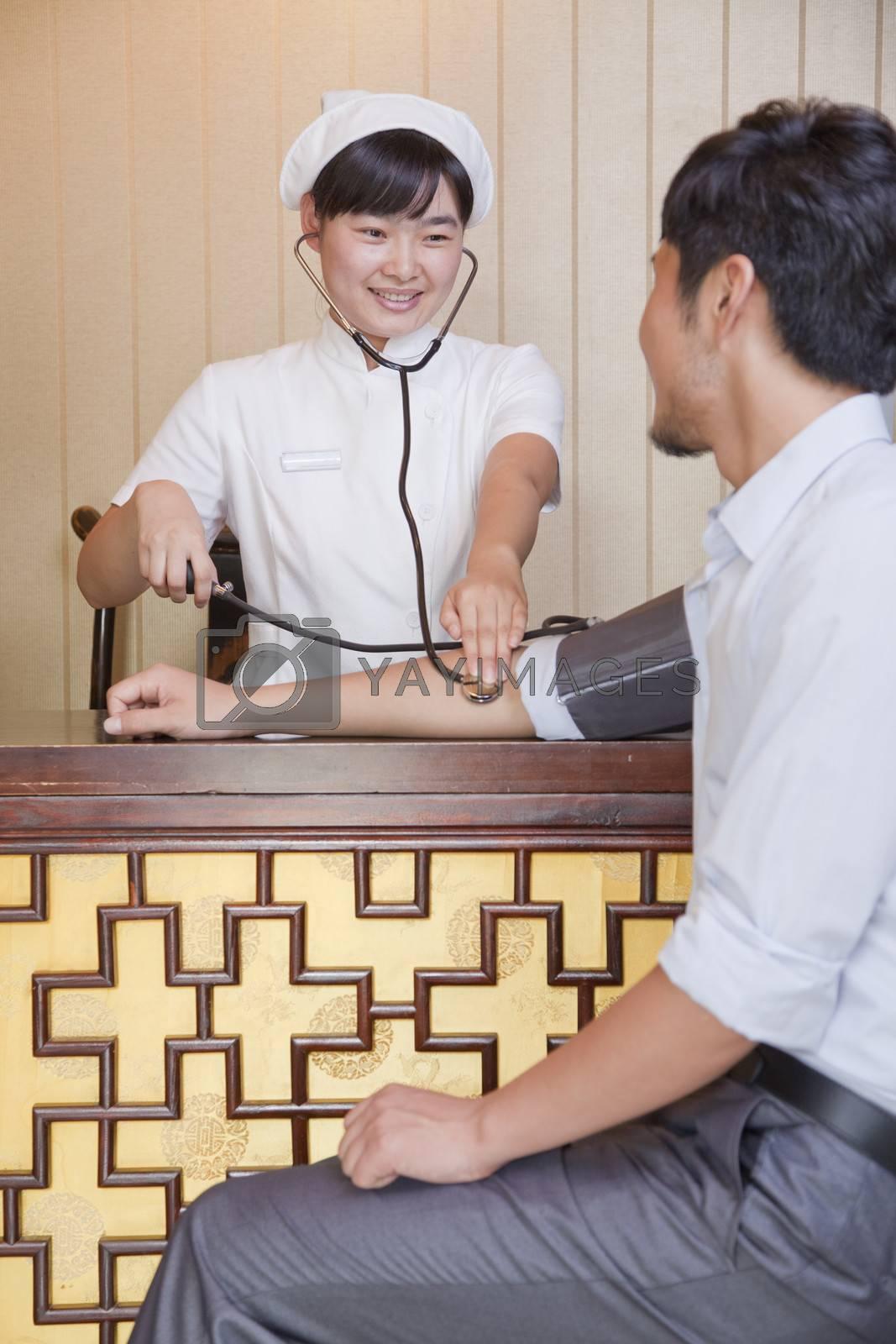 Nurse Checking Businessman's Blood Pressure