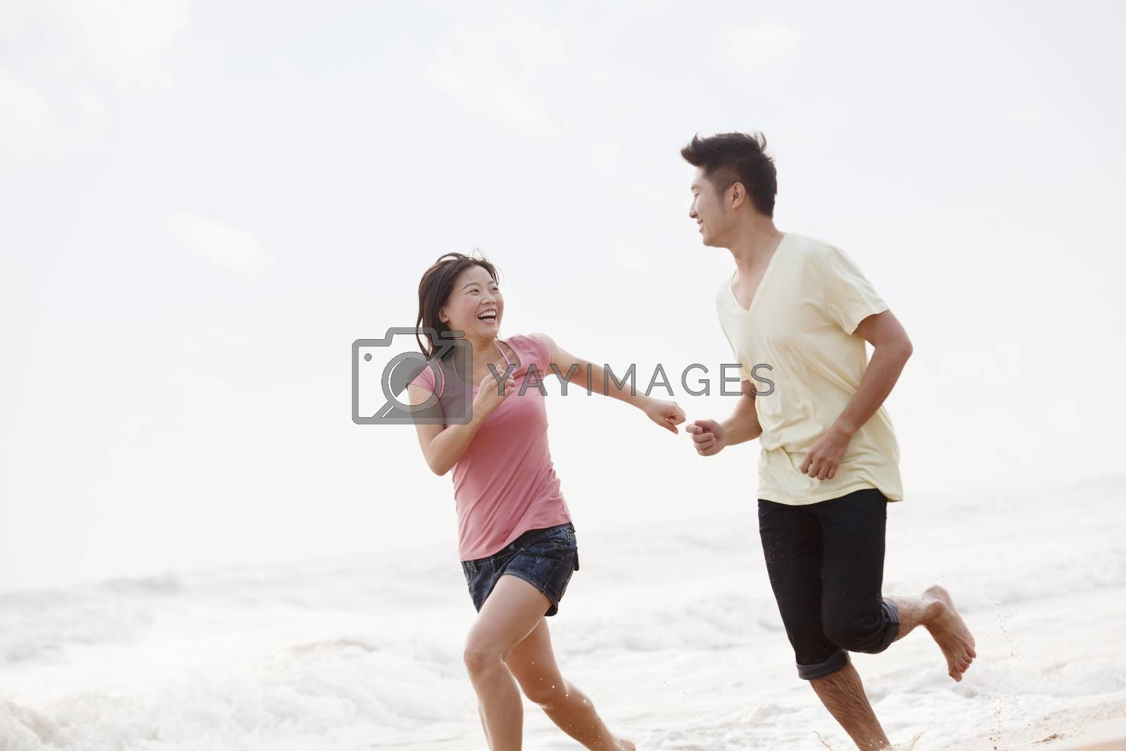 Couple running by the waters edge on the beach, China