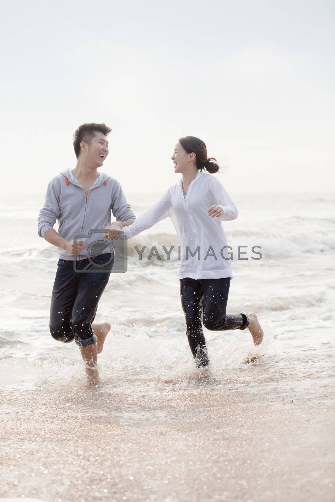 Young couple holding hands and running by the waters edge on the beach, China