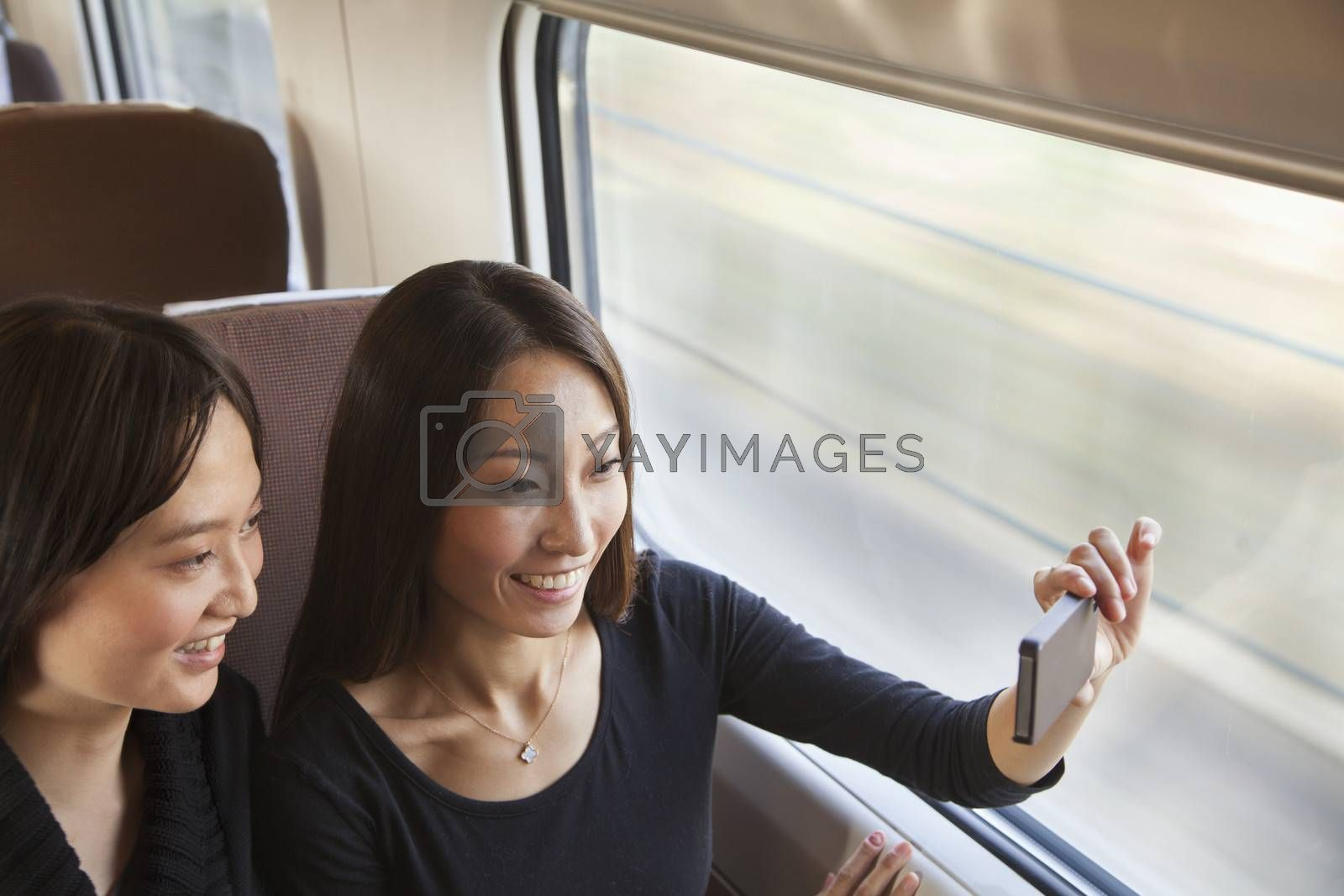 Two Friends Taking a Picture Out the Train Window