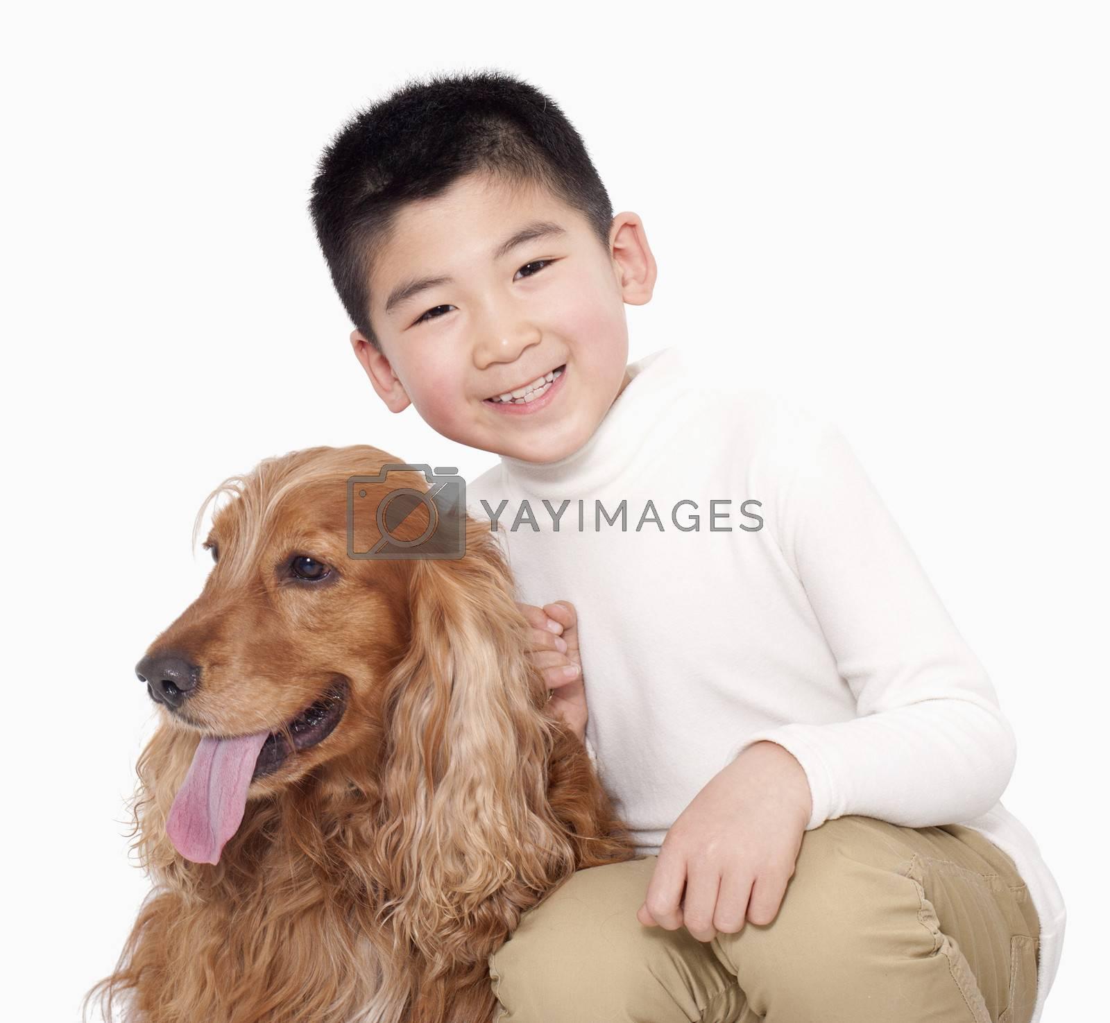 Portrait of Boy sitting next to his dog, studio shot