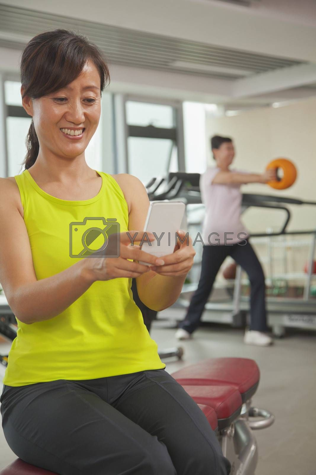 Mature woman using her cell phone in the gym