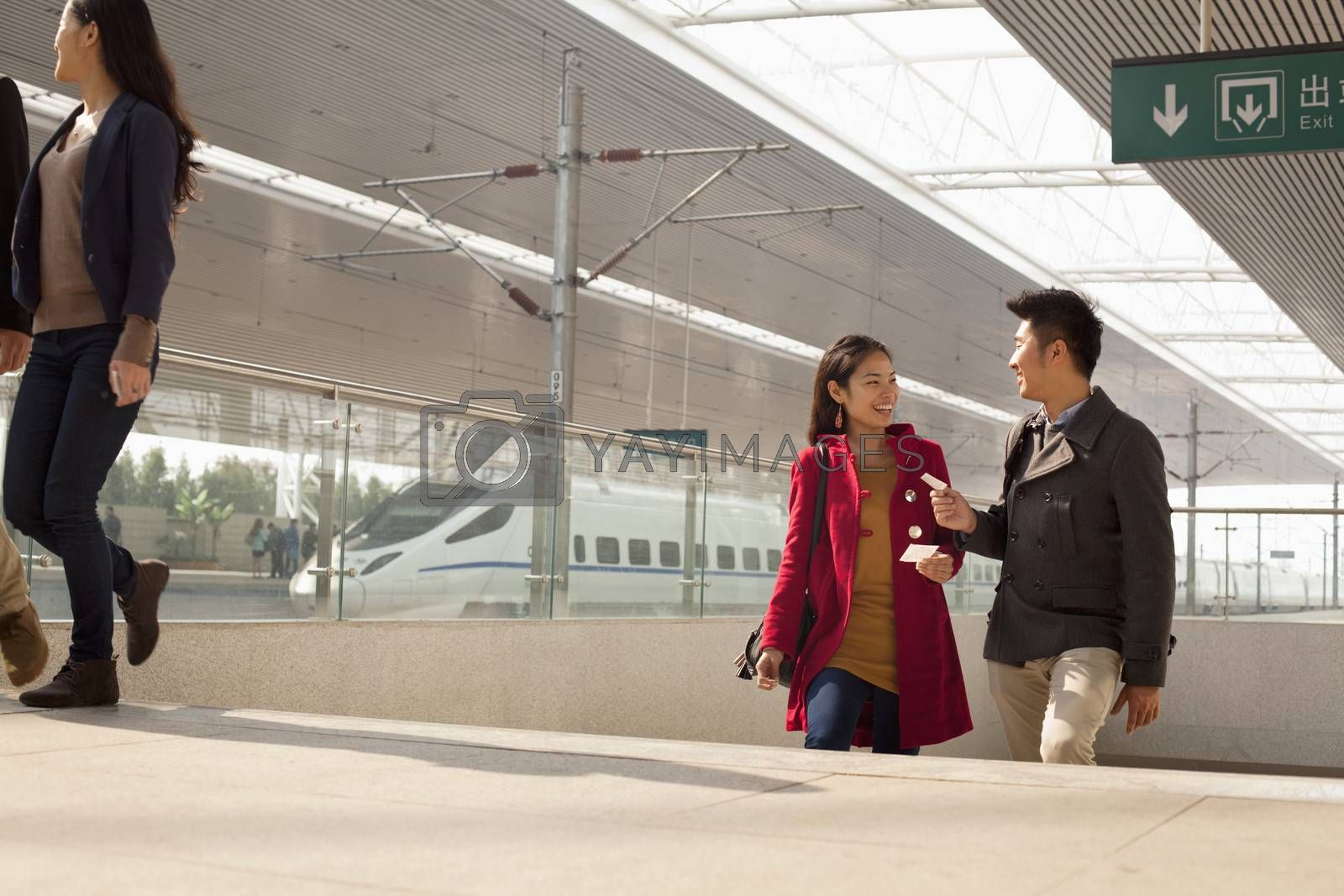 Young woman talking to man on railway platform, China