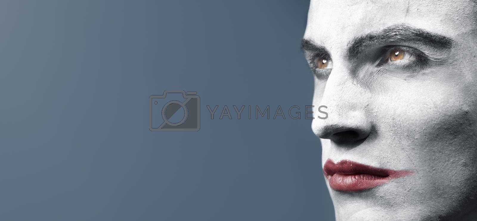 Male head with face-paint outdoors during twilight. Creative colors and darkness added. Horizontal photo with empy space