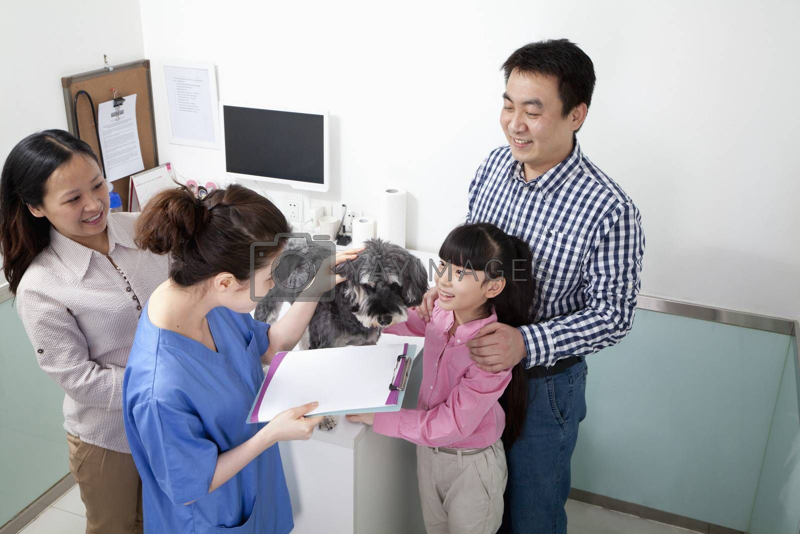 Family with pet dog in veterinarian's office by XiXinXing