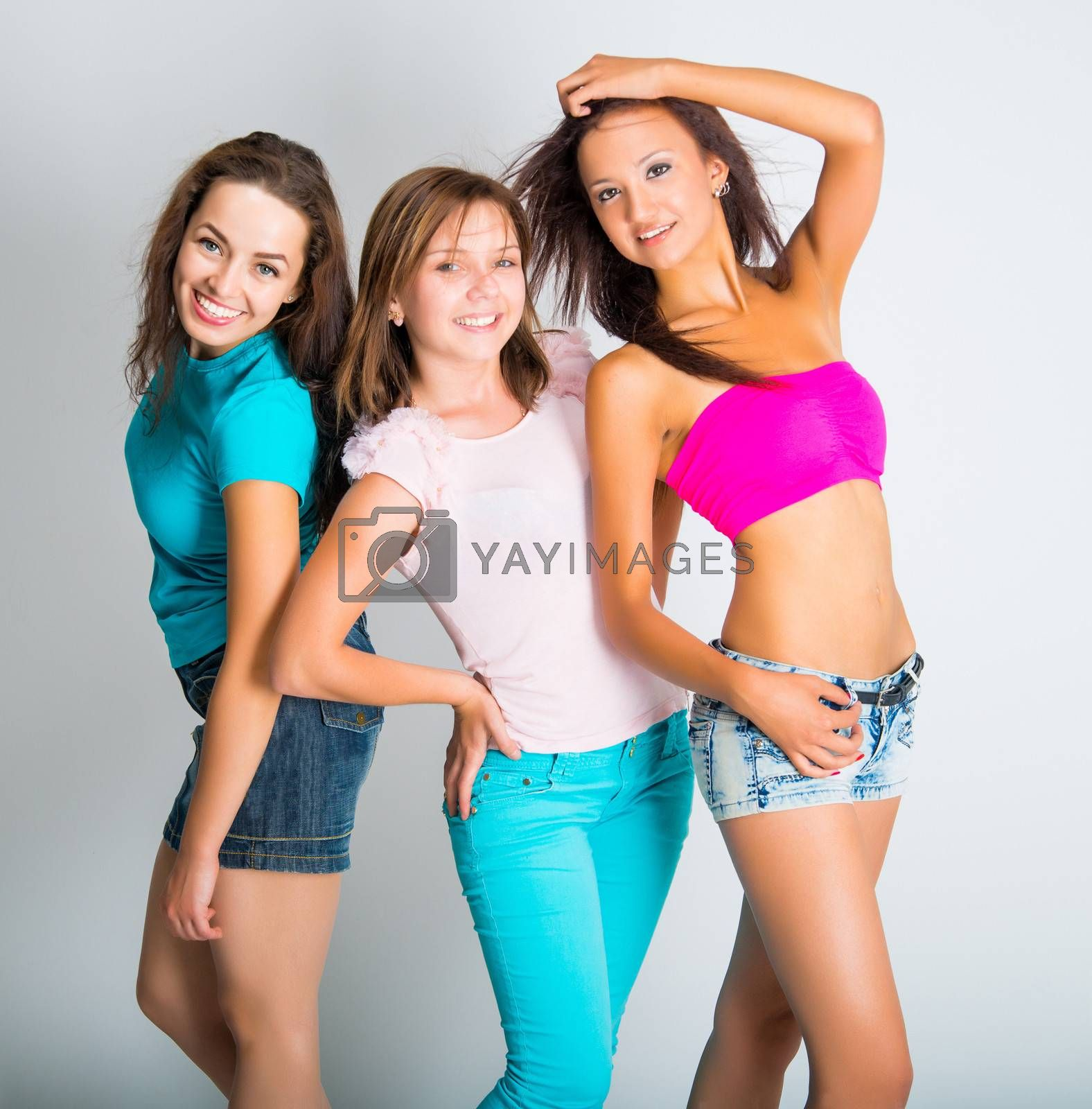 three teenage girls smiling on light background
