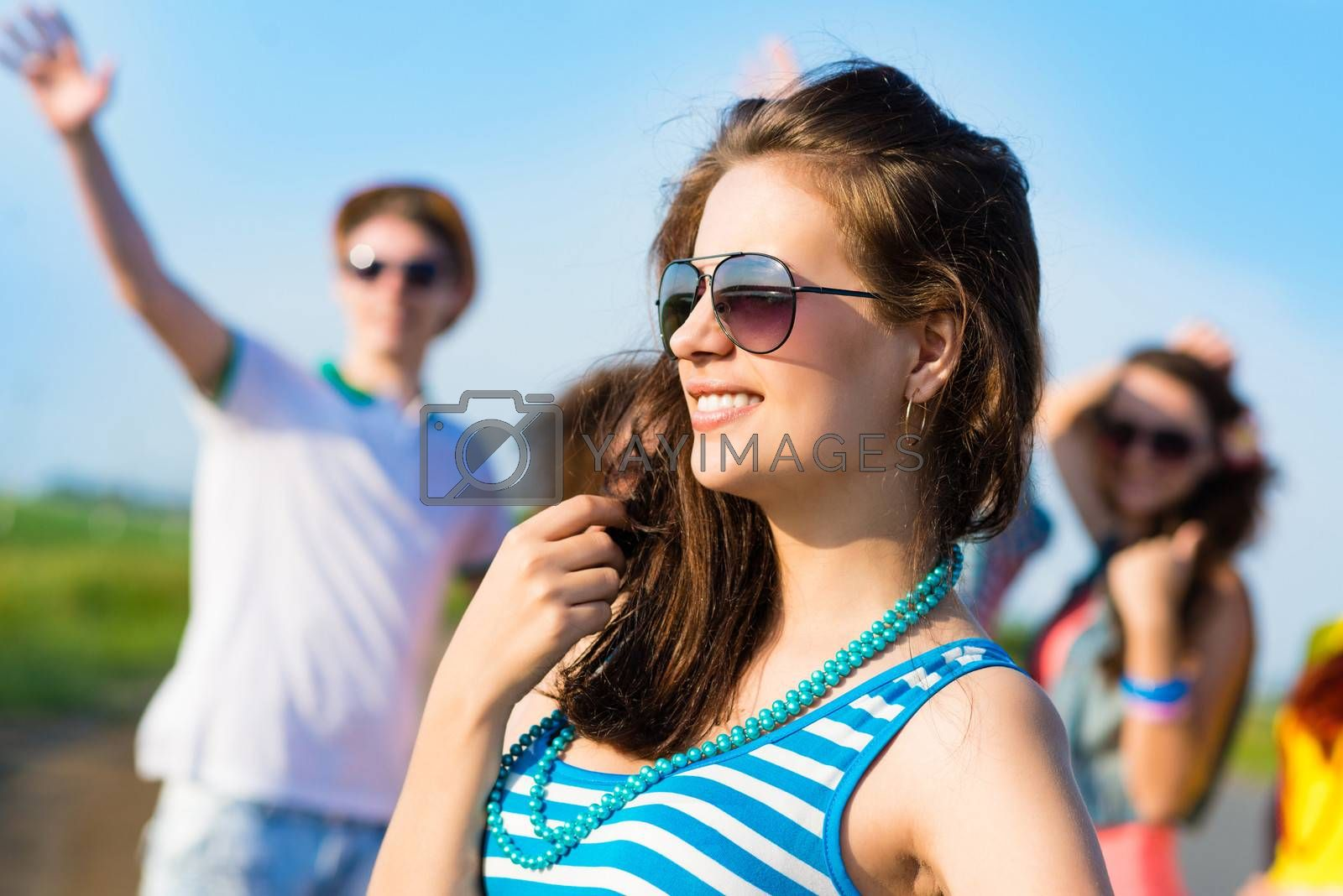 stylish young woman in sunglasses on the background of blue sky and friends