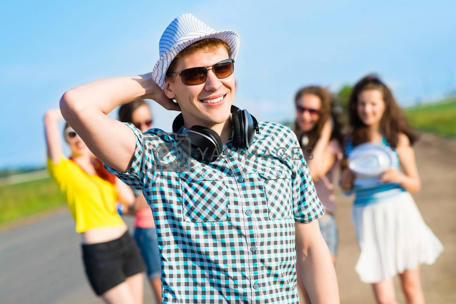 young man in sunglasses, a hat holds a hand on a background of blue sky and friends