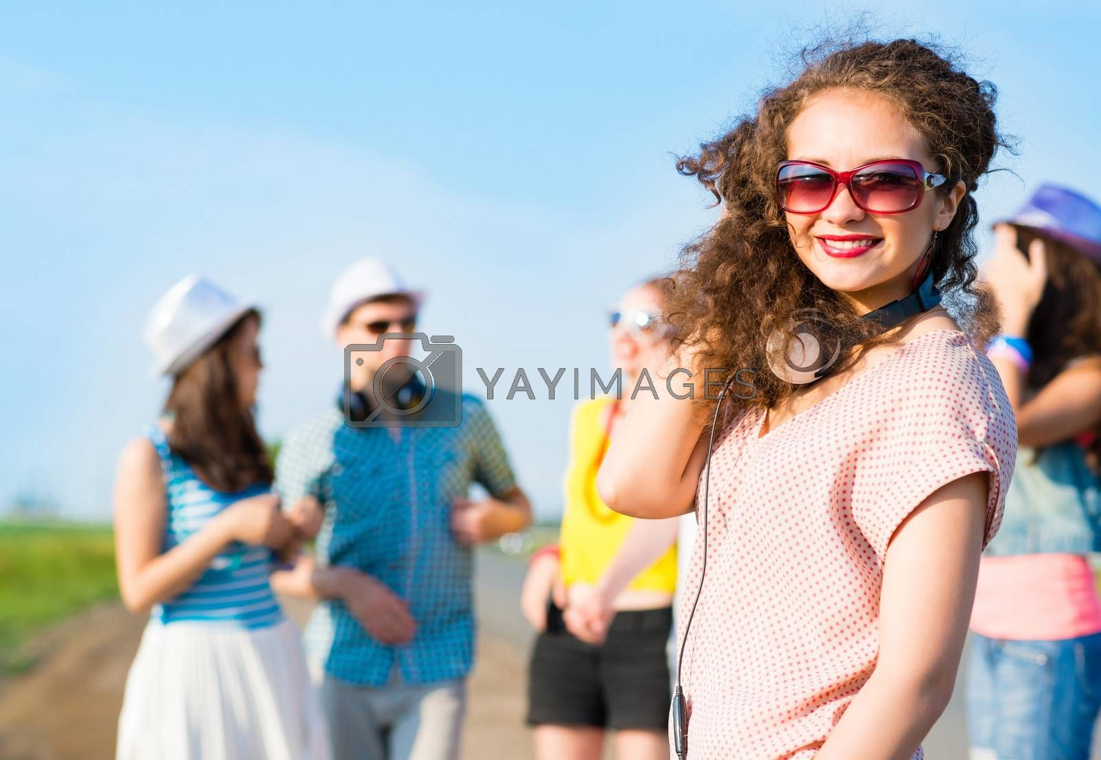 young woman with headphones on a background of blue sky and funny friends