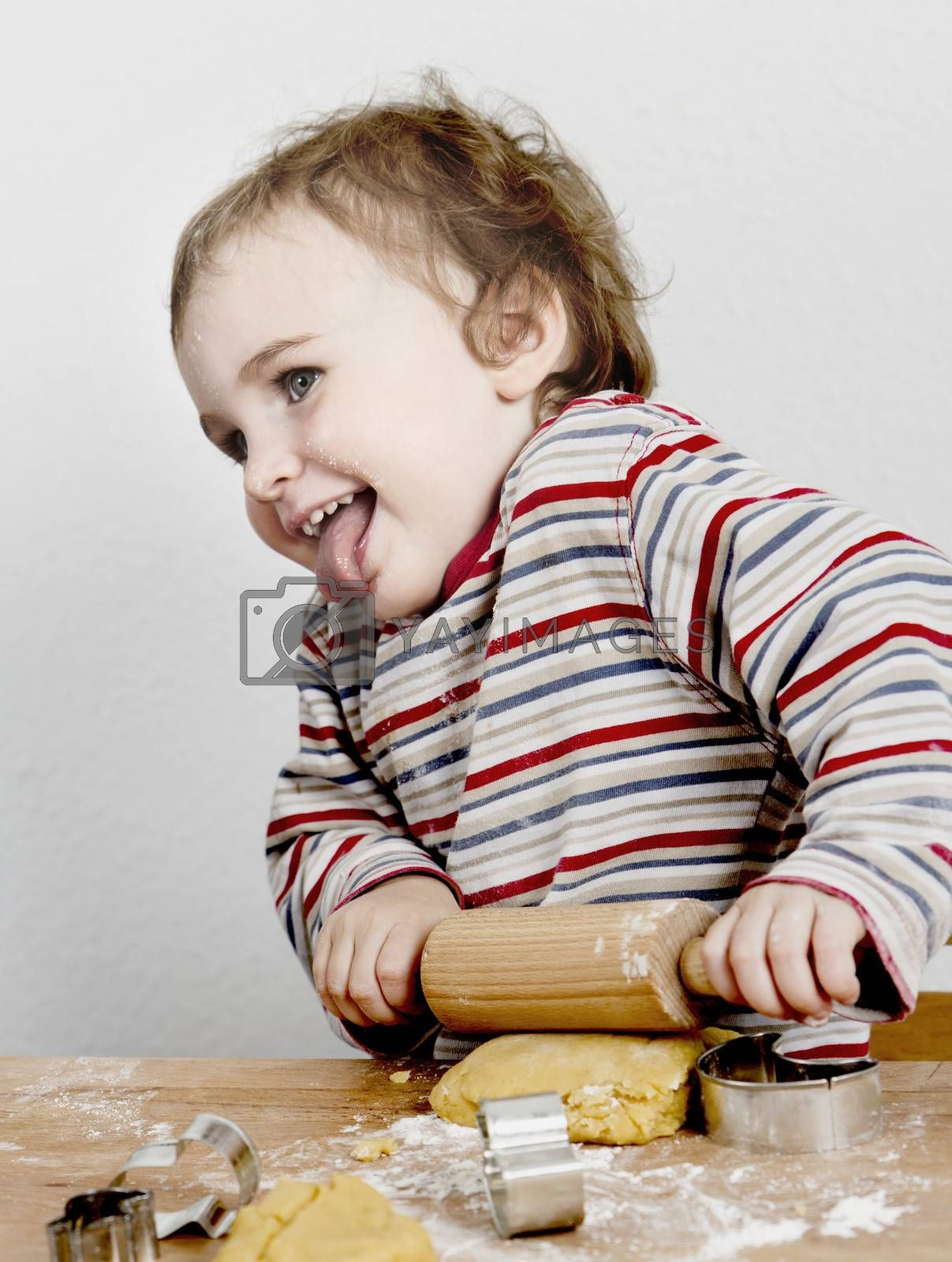cute, laughing child with dough and rolling ping grey background. horizontal image