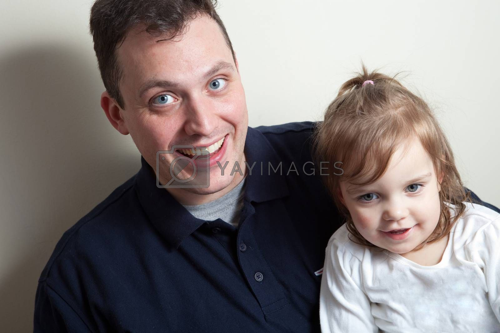 A young happy toddler aged little girl posing with her daddy.