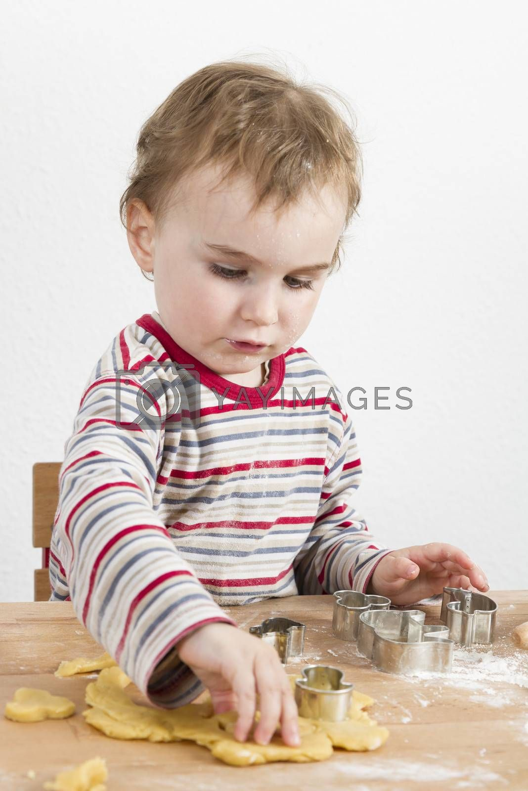 young child in vertical image looking at baking tools and dough