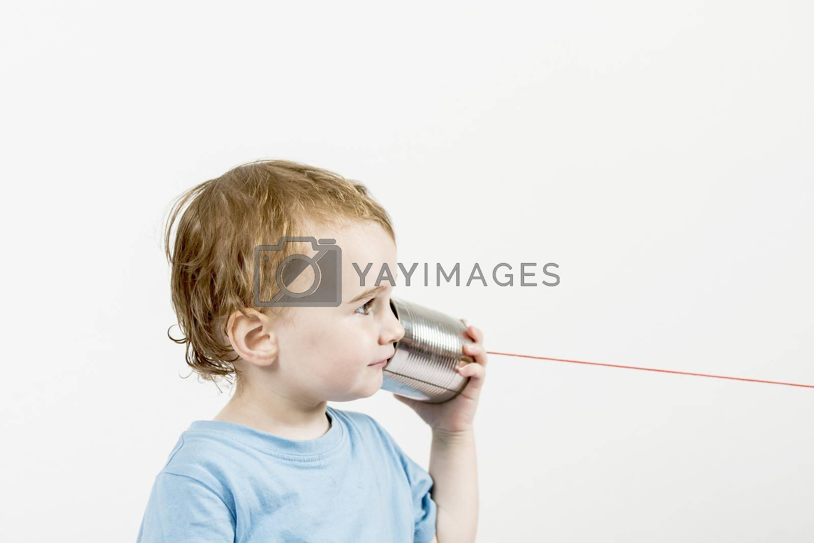 young child in grey background listening to tin can phone. horizontal image