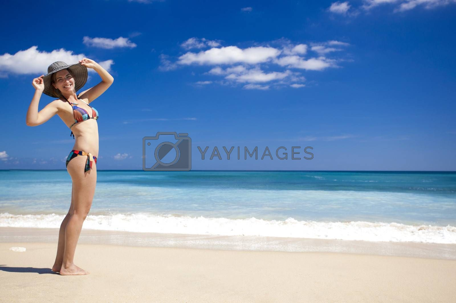 Beautiful young woman enjoying the summer in a tropical beach