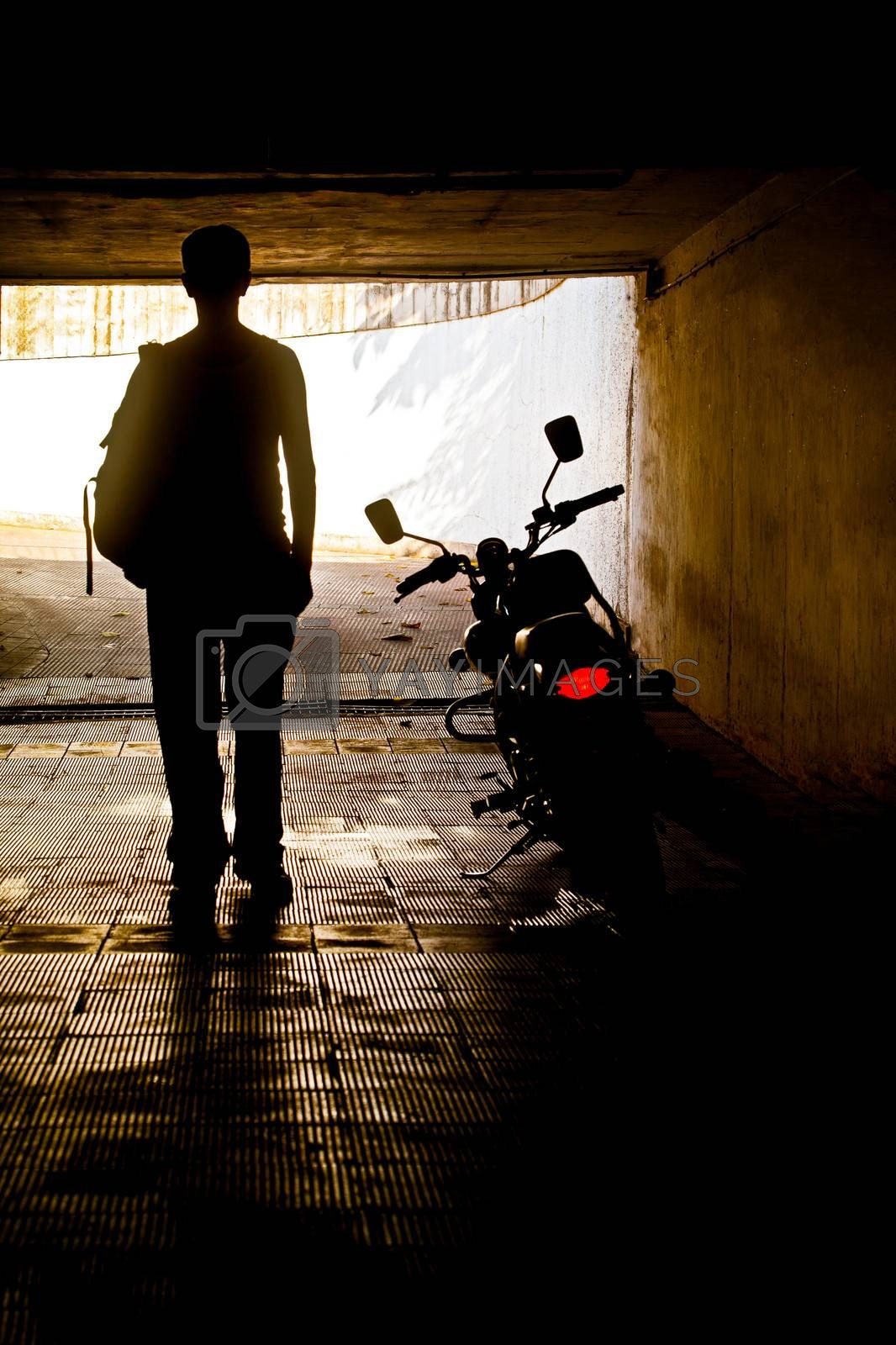 Vertical silhouette concept capture of a man in a vest with ruck sack back pack near his motorcycle which has its tail slights switched on in a tunnel