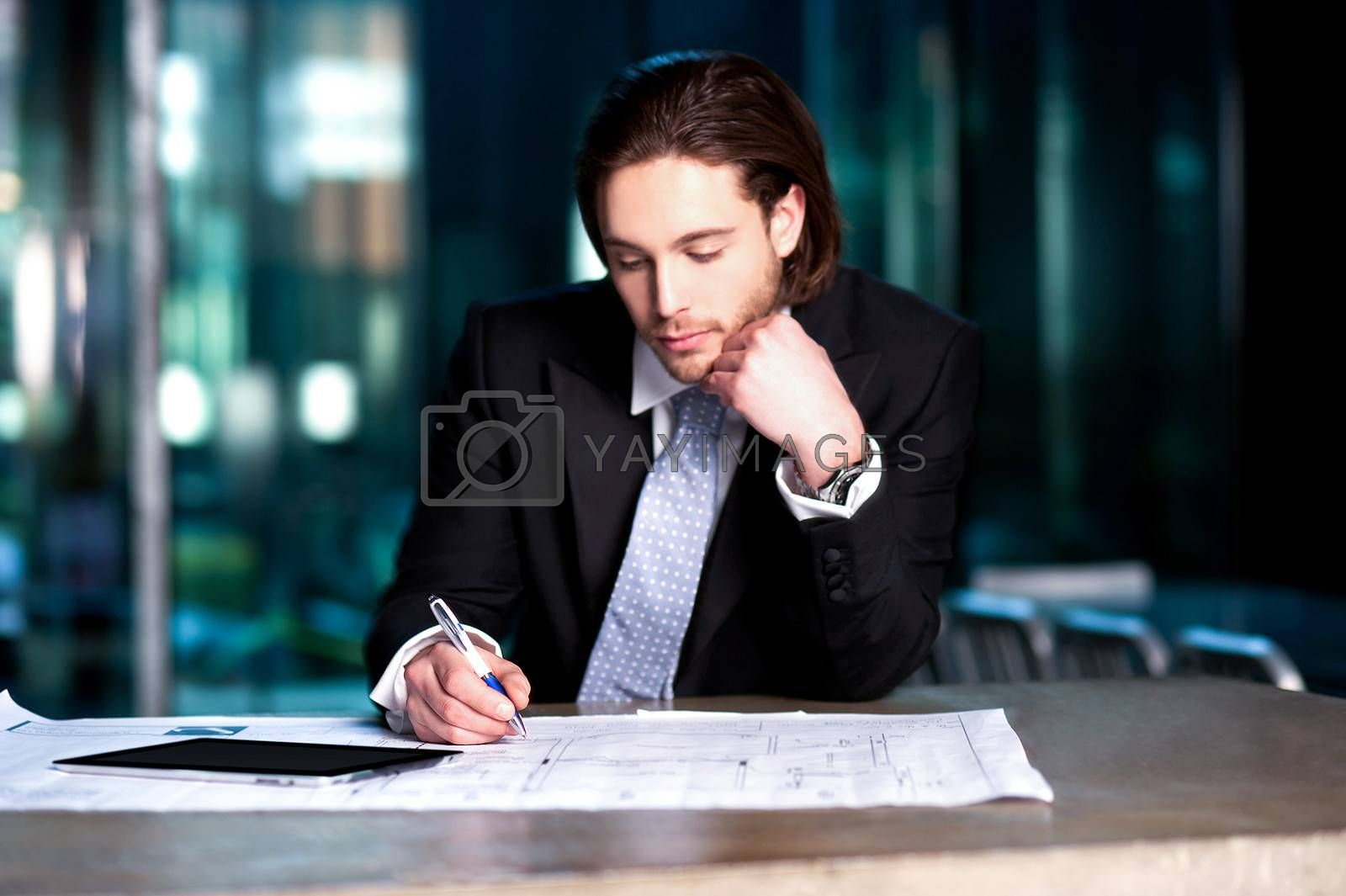 Handsome young businessman busy with his financial year planning.