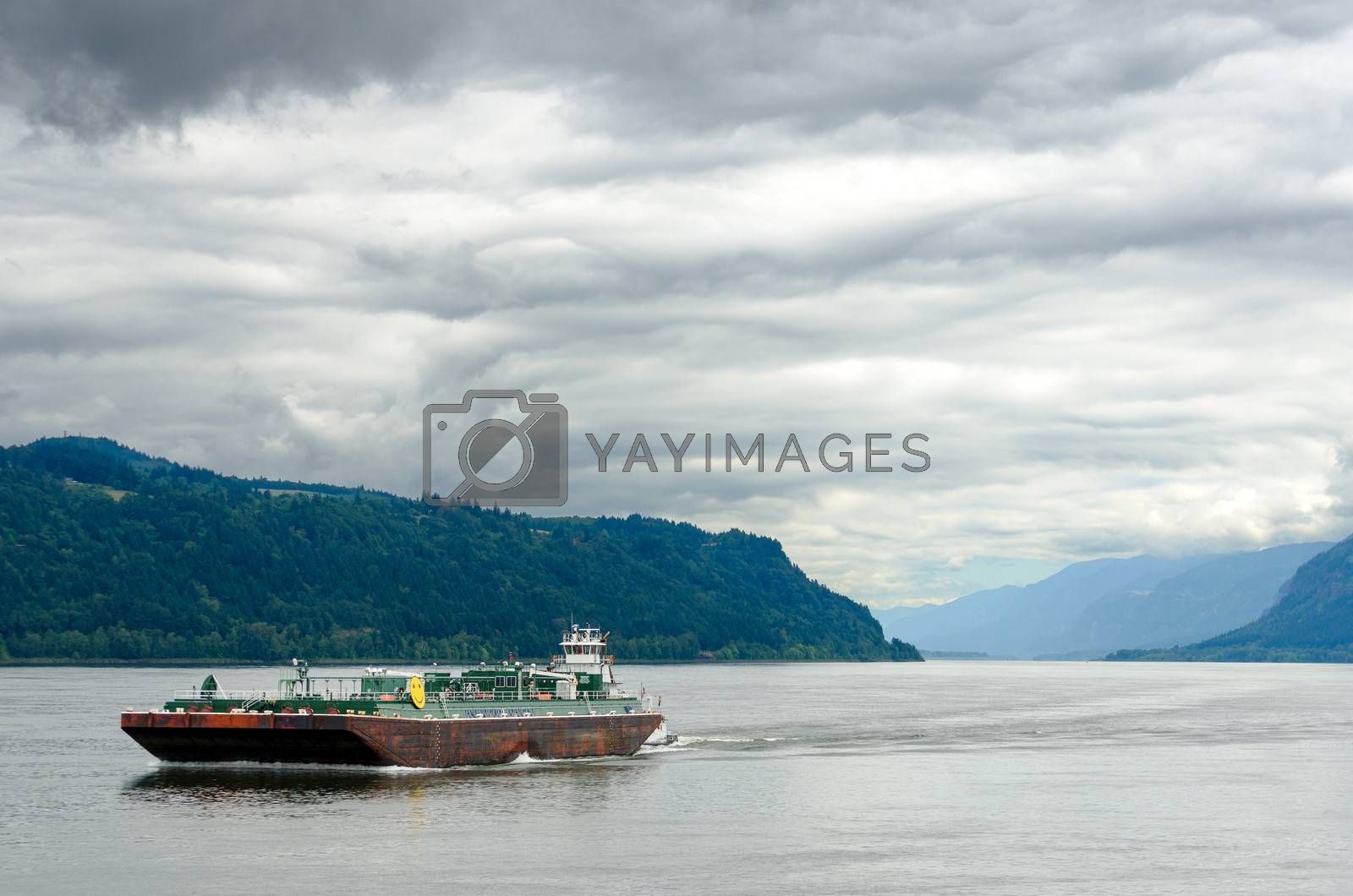 A barge passing through the Columbia River Gorge between Oregon and Washington