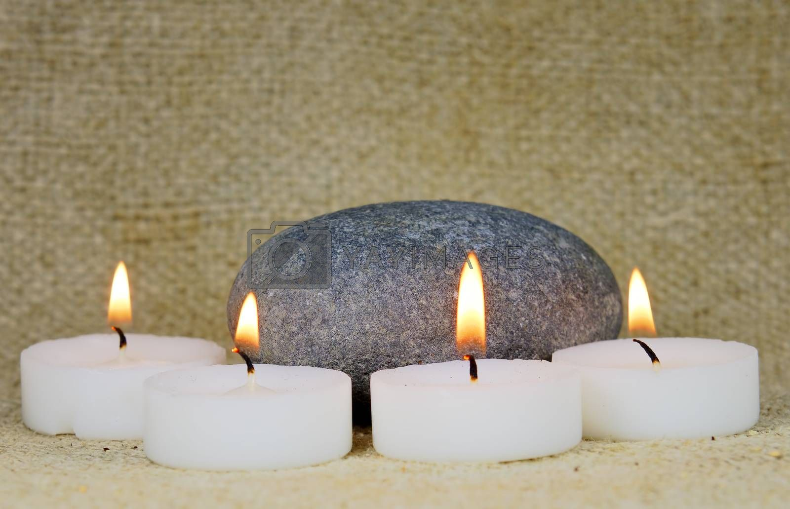 pebble surrounded by candles