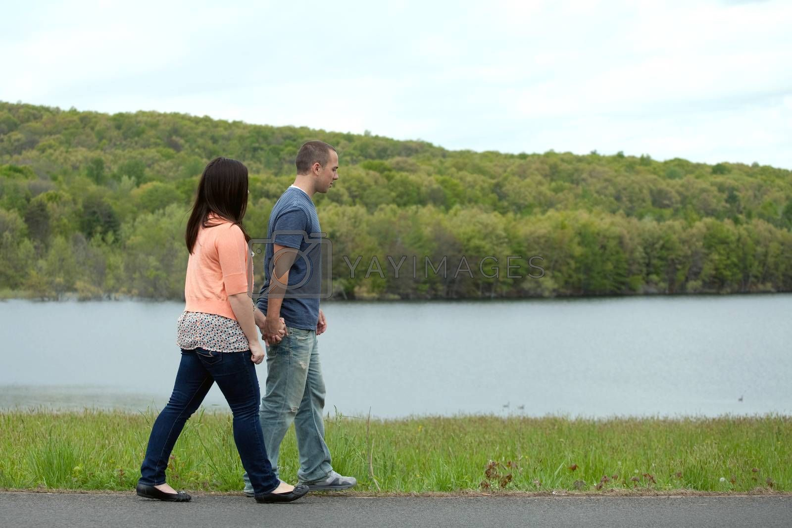 Young happy couple enjoying each others company outdoors walking by the water.