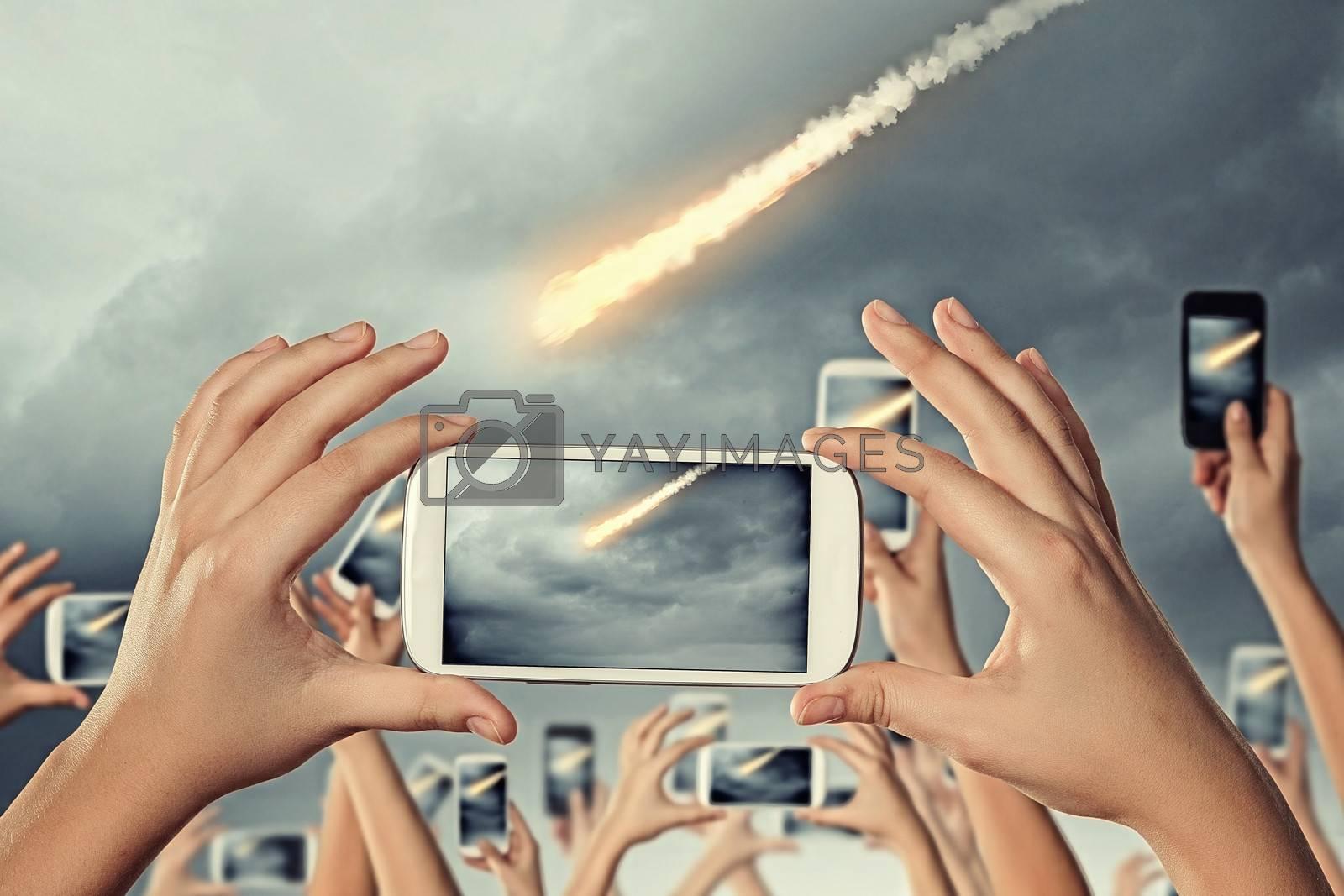 Close up of human hands taking photo of falling meteorite