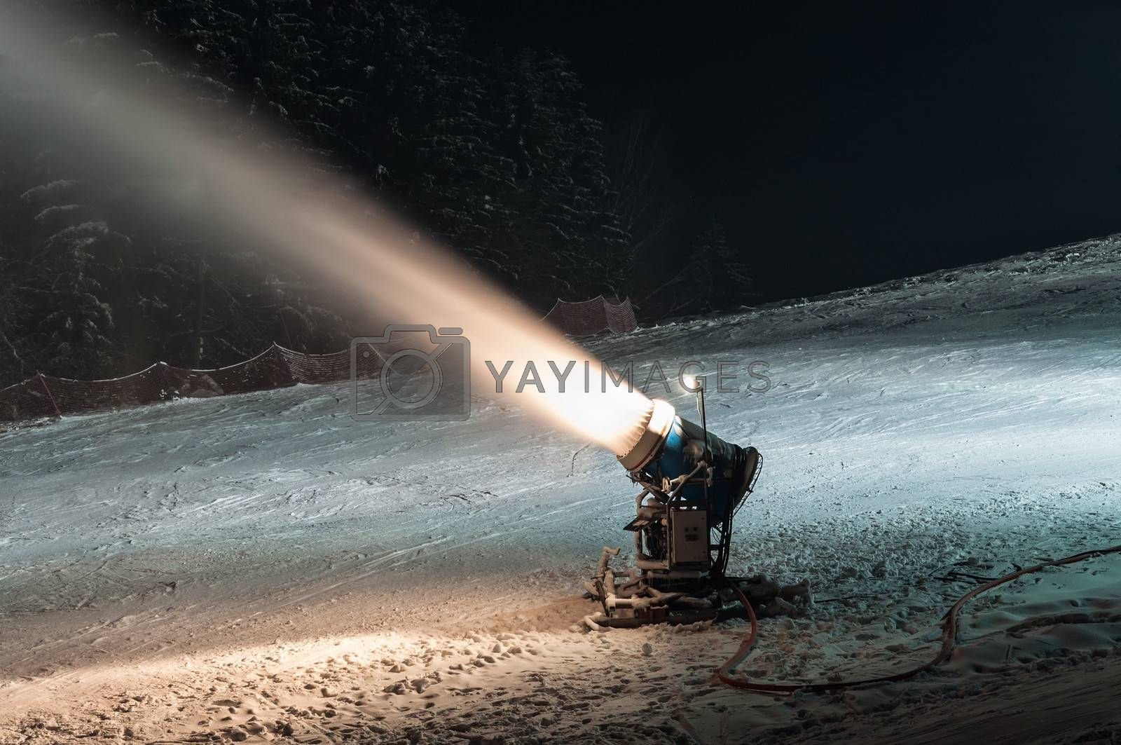 Working snow cannon at night on ski slope.