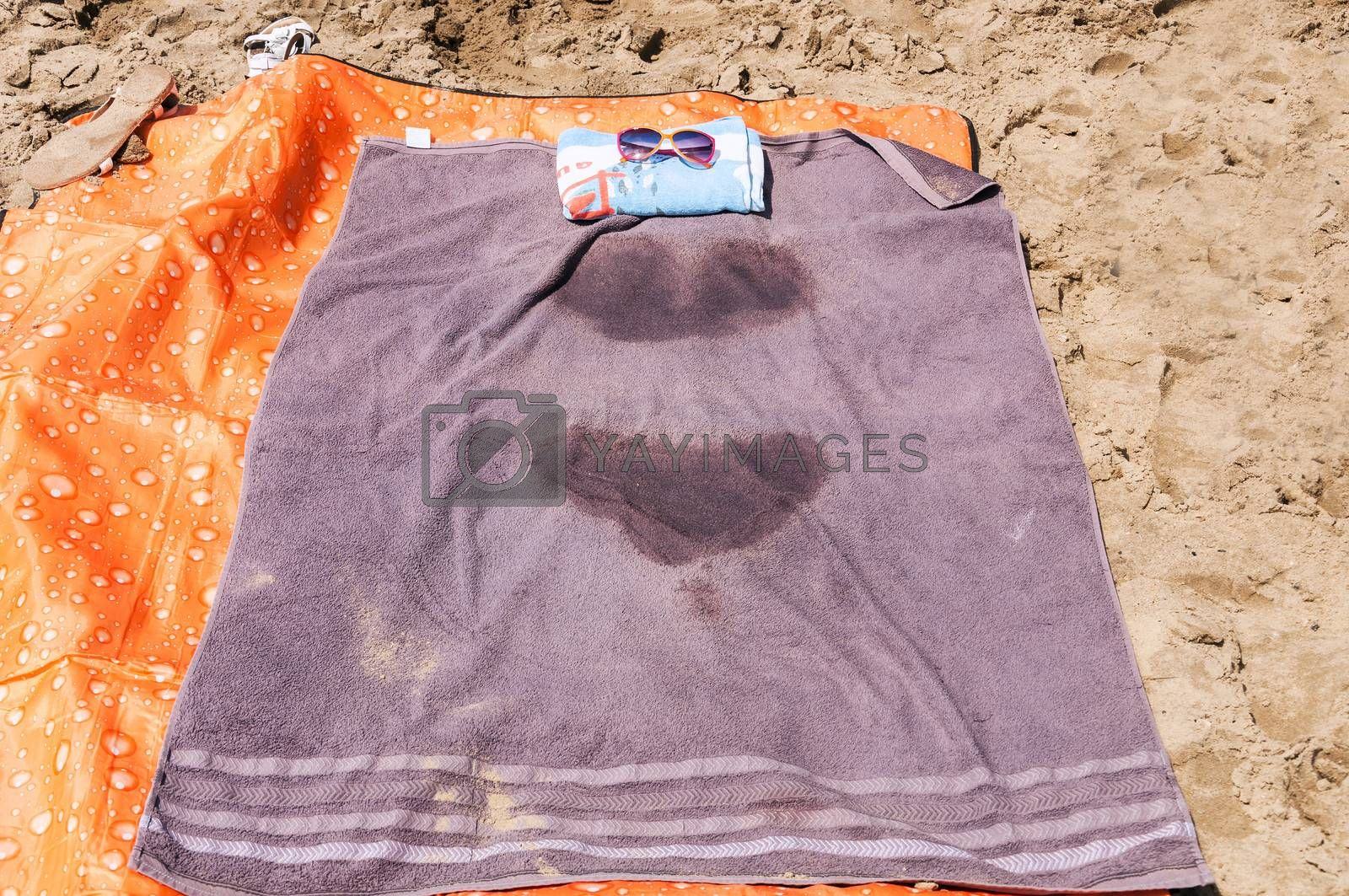 A towel with wet spots laying on the beach.