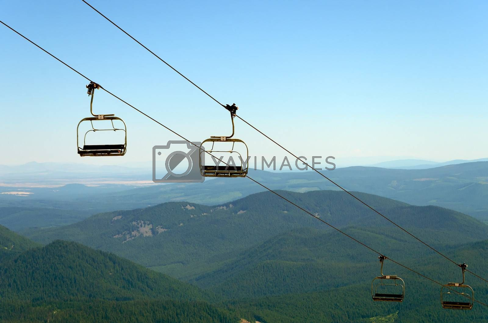Chairlift on Mount Hood with green pine tree covered hills in the background