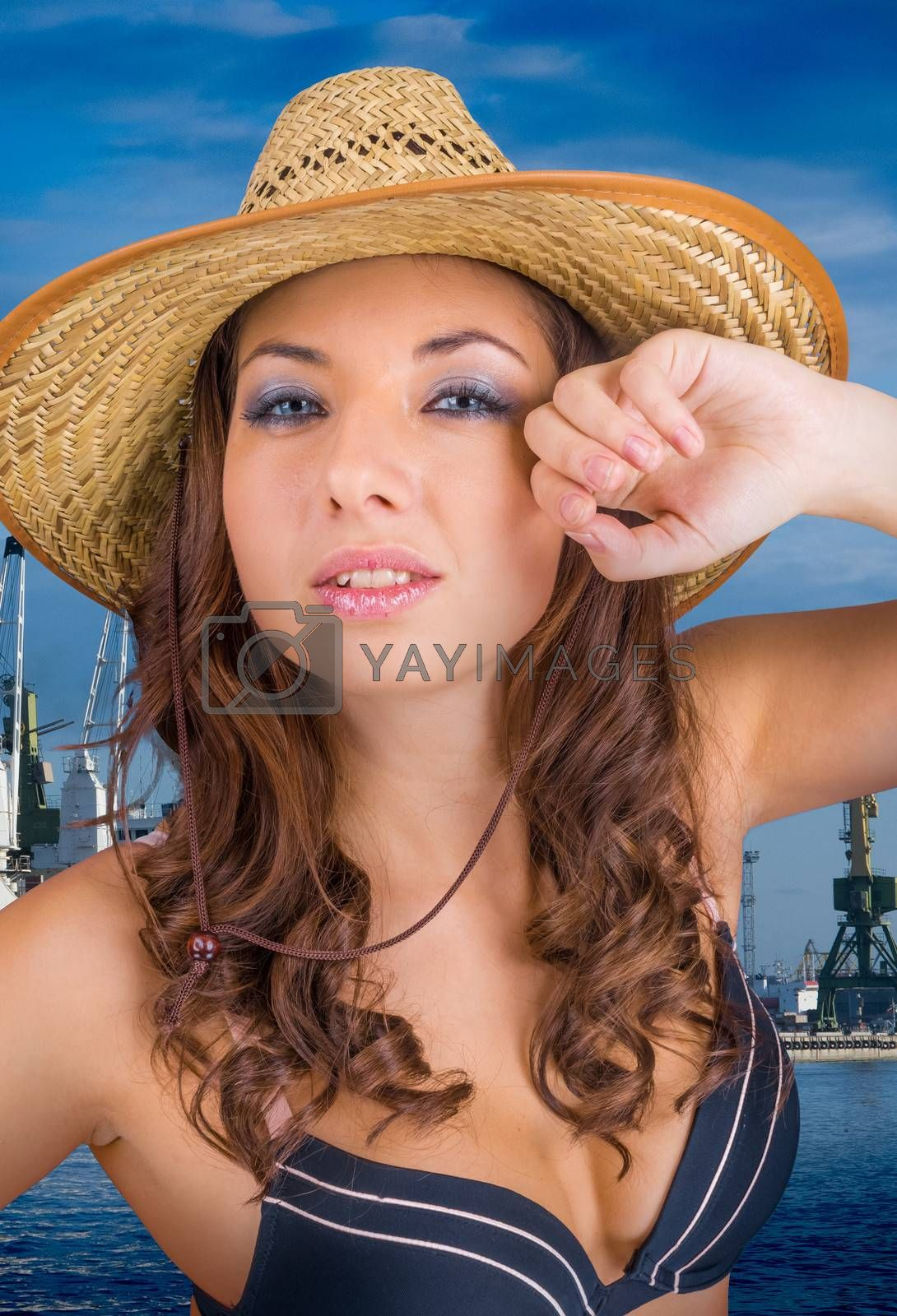sexy lady in her bra and hat on the background of the sky and the sea in the sea port
