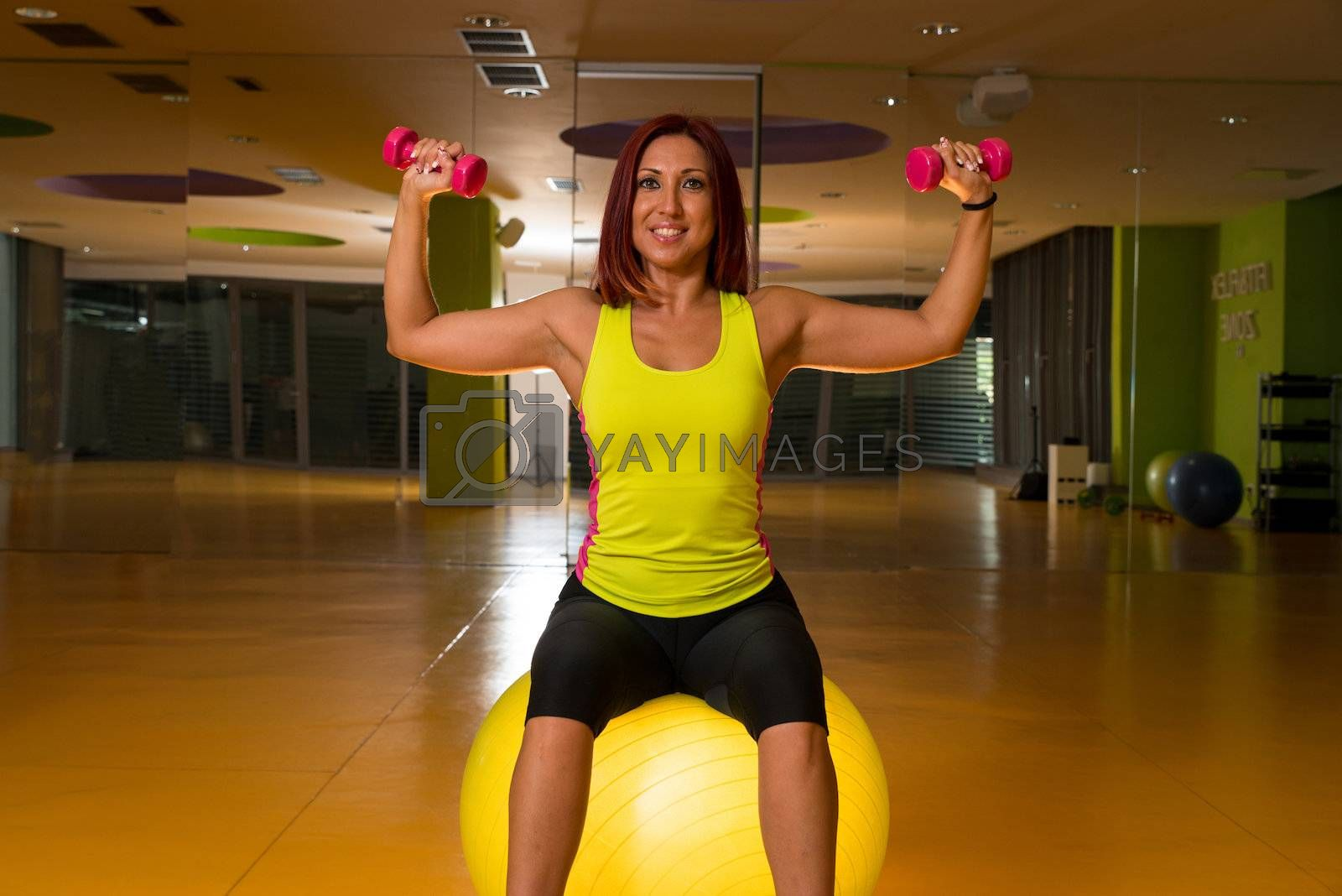 Woman doing fitness exercises with dumbbells