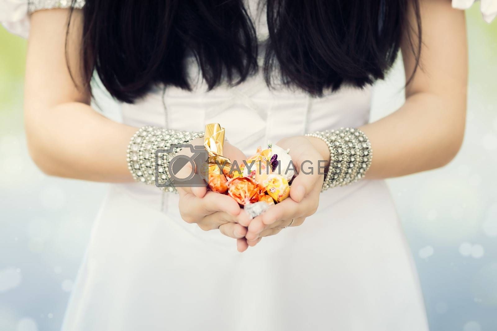 Close up on girl's hands offering candy.