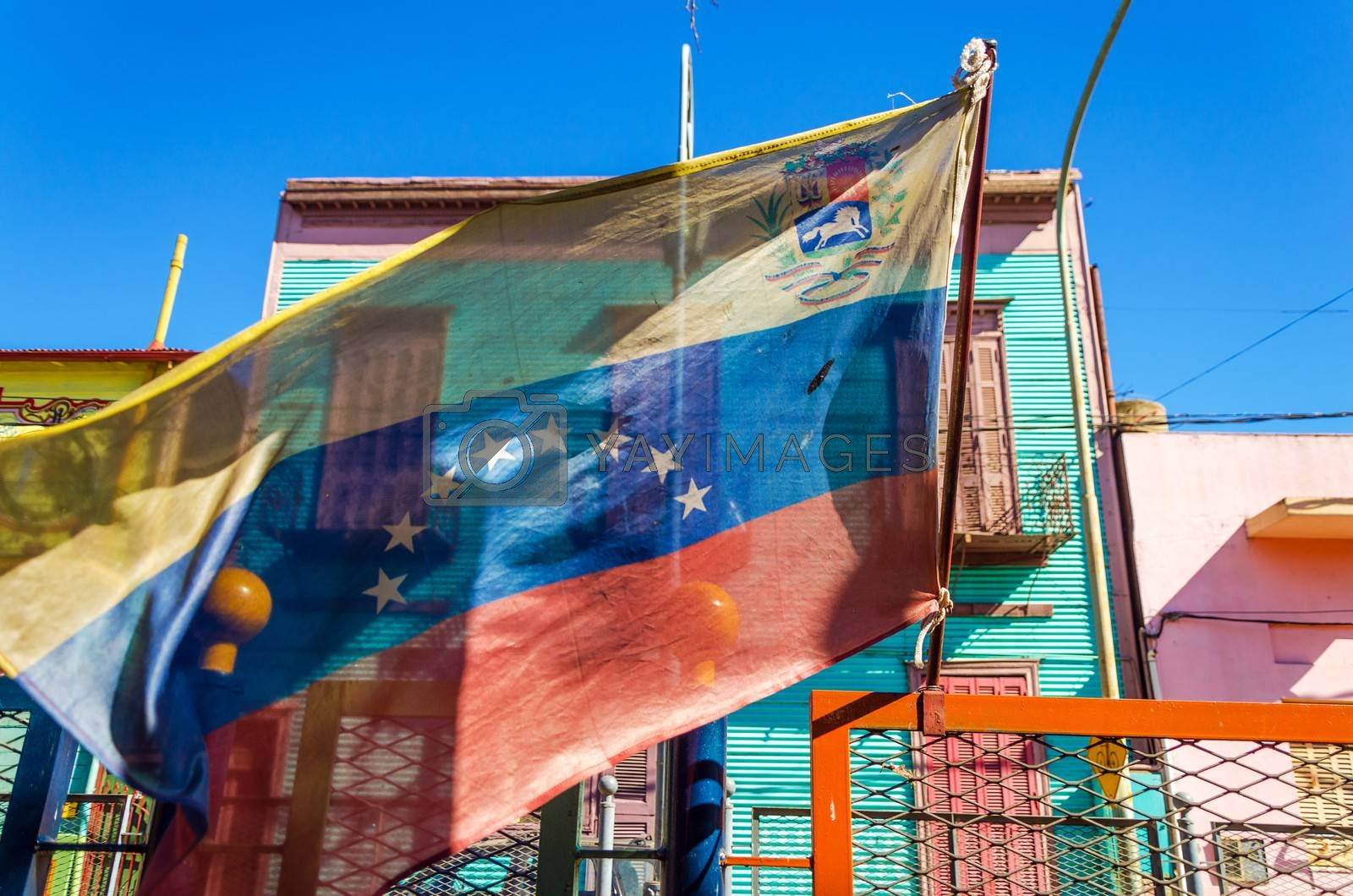 Venezuelan flag blowing in the wind with brightly colored buildings