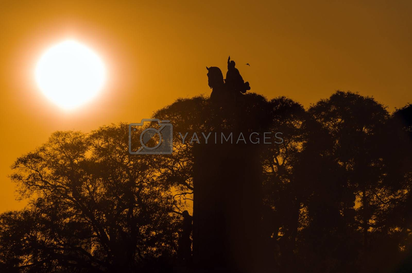 The sun rising of a statue in the Recoleta neighborhood of Buenos Aires, Argentina
