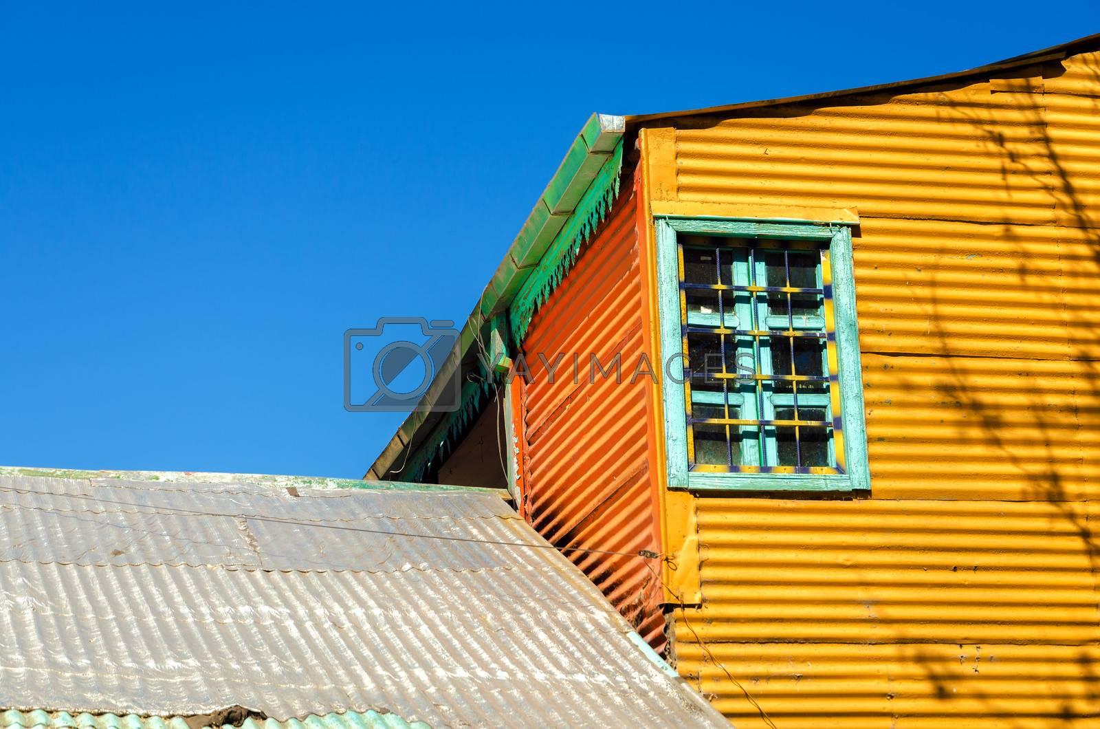 Old orange building set against a blue sky in La Boca neighborhood of Buenos Aires